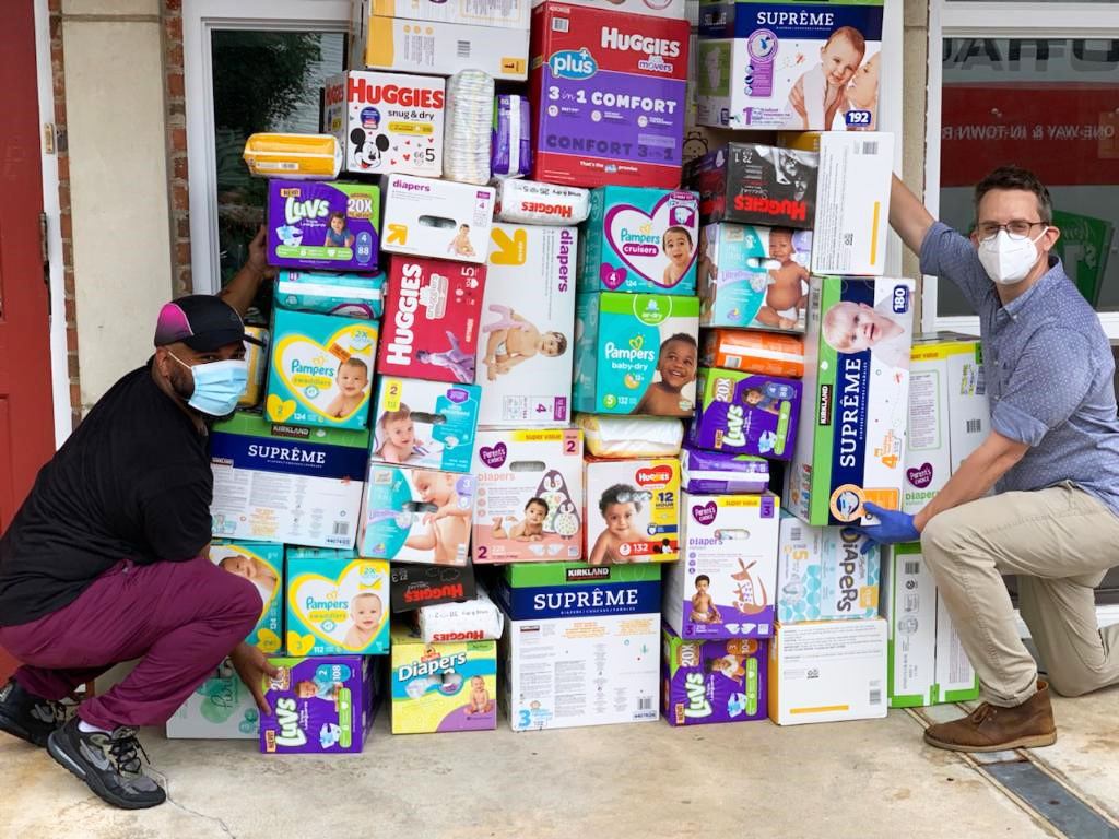 Two people wearing masks pose next to a collection of bulk diaper boxes