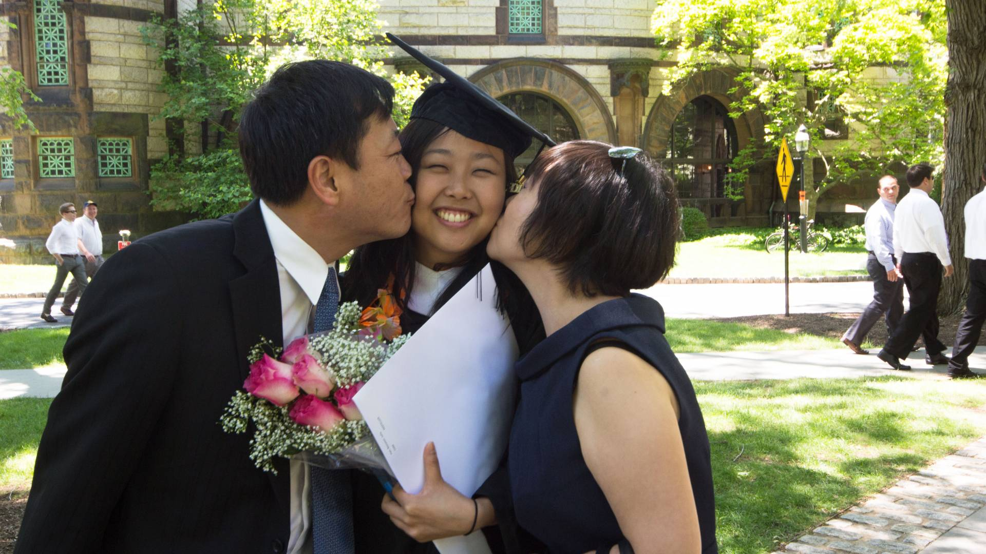 Photo of Parents congratulating their daughter at Commencement with a kiss