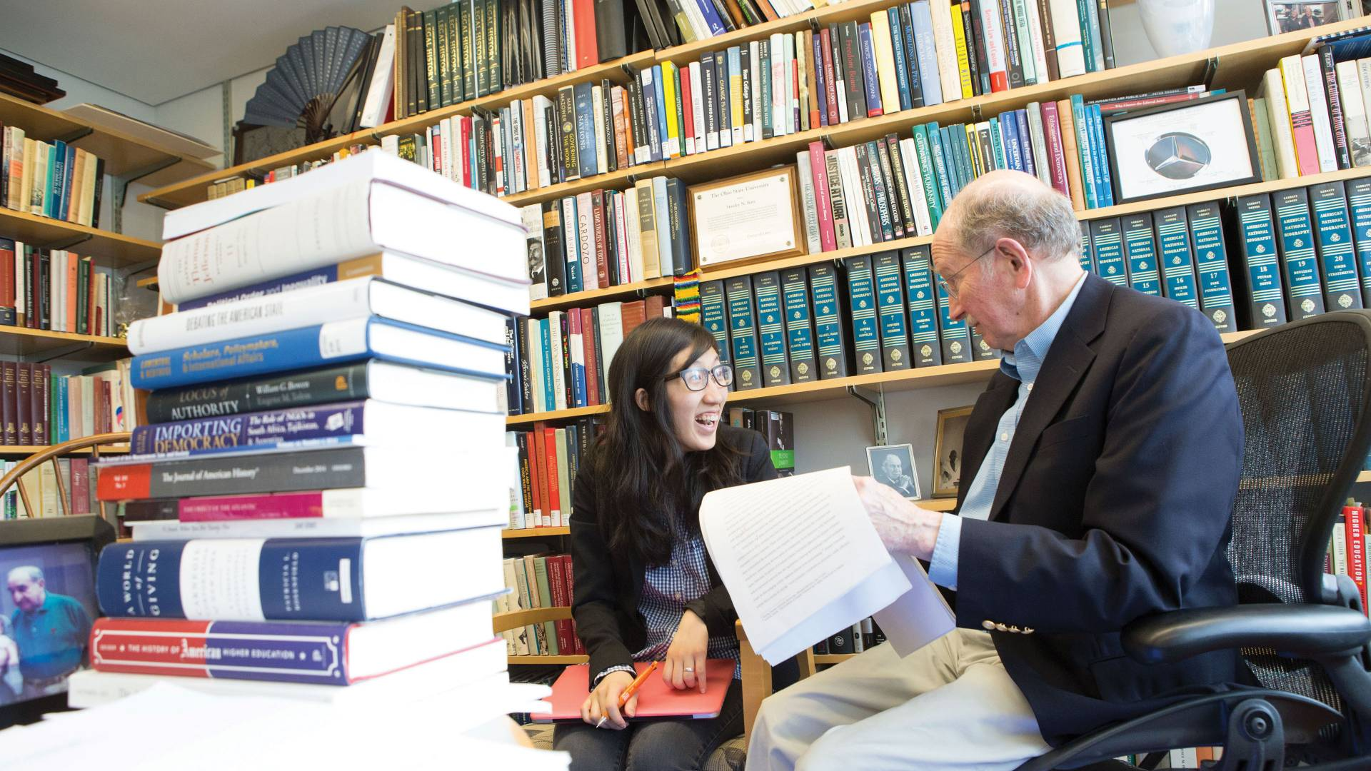 A student and professor sit and talk during an advising session, surrounded by books