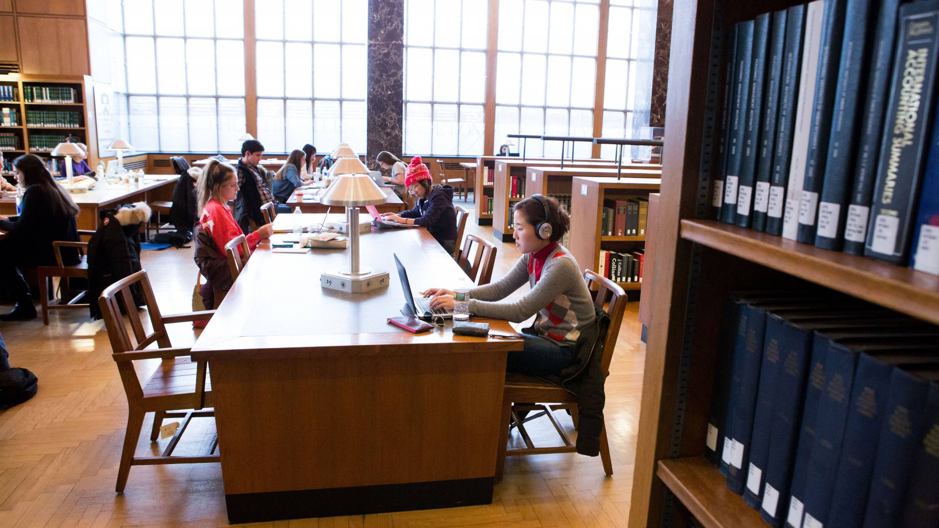 Students study at tables in firestone library in front of large windows