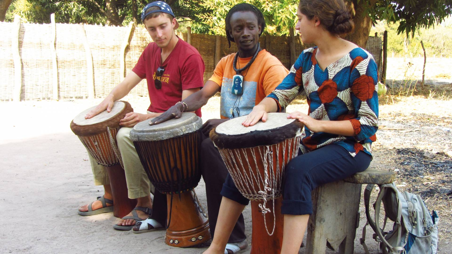 Students sit and play drums with drummer in Senegal
