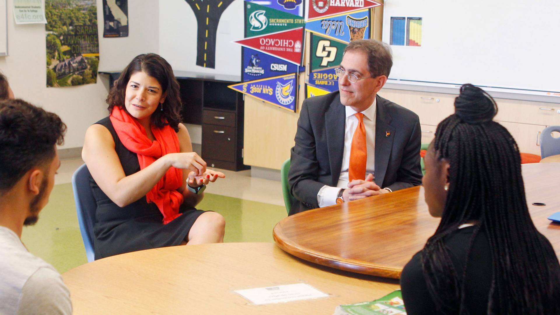 President Eisgruber and Khristina Gonzalez sit at a table, speaking with high school students