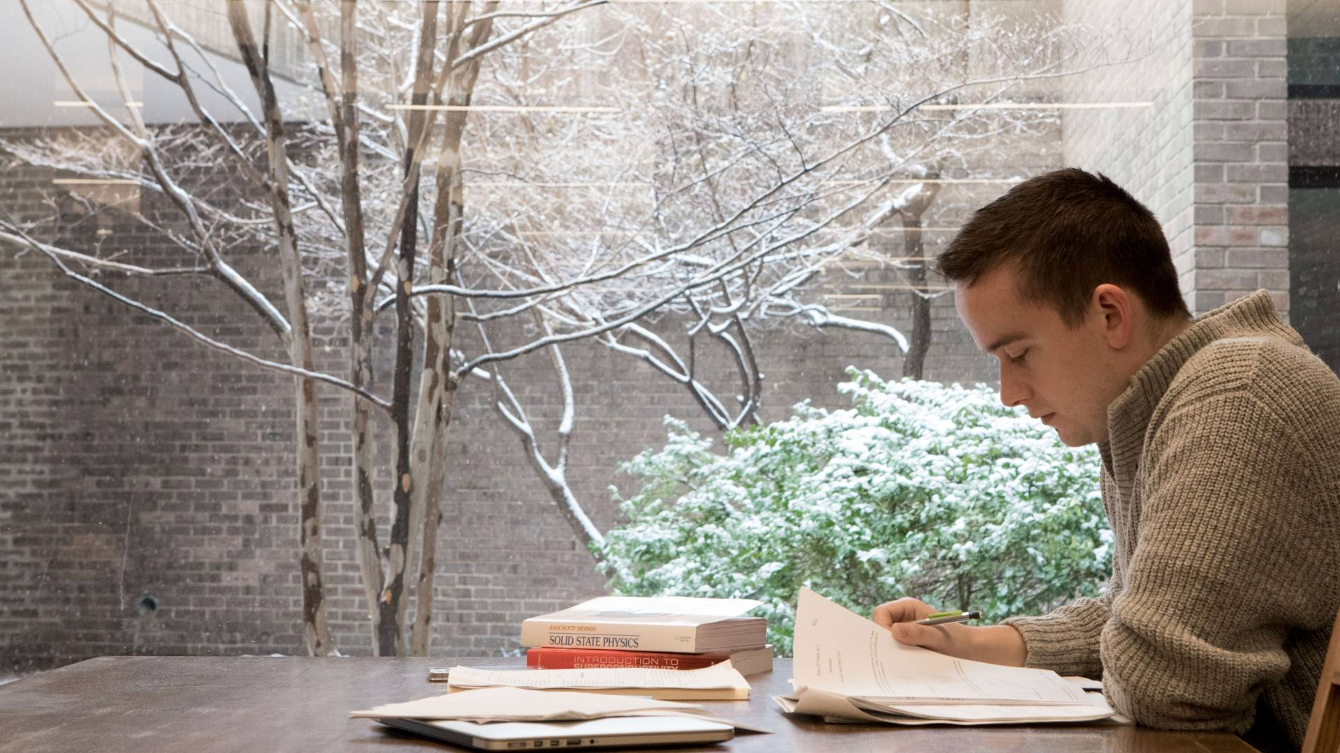 Student studying against window showing snow outside