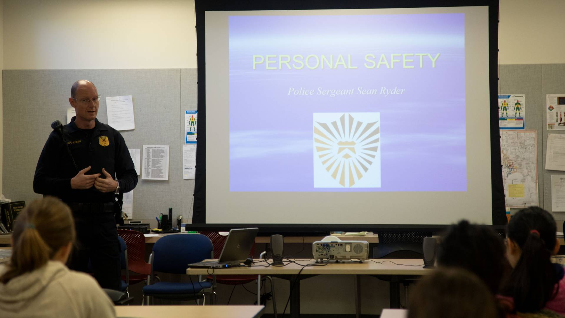 Public Safety officer Sean Ryder teaching safety course; Text on Slide: Personal Safety; Police Sergeant Sean Ryder