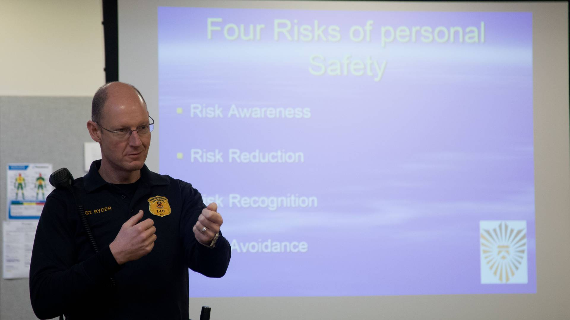Public Safety officer Sean Ryder teaching safety course; Text on Slide: Four Risks of Personal Safety; Risk Awareness; Risk Reduction; Risk Recognition; Risk Avoidance