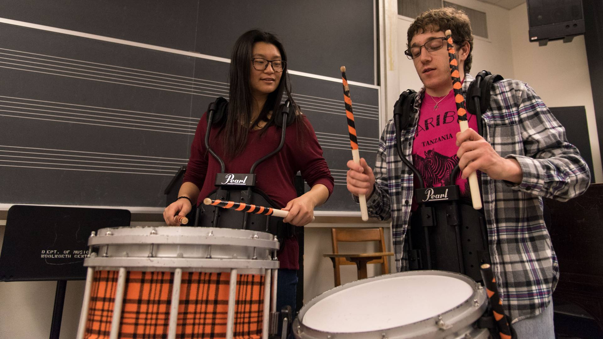 Student demonstrating drums to another student