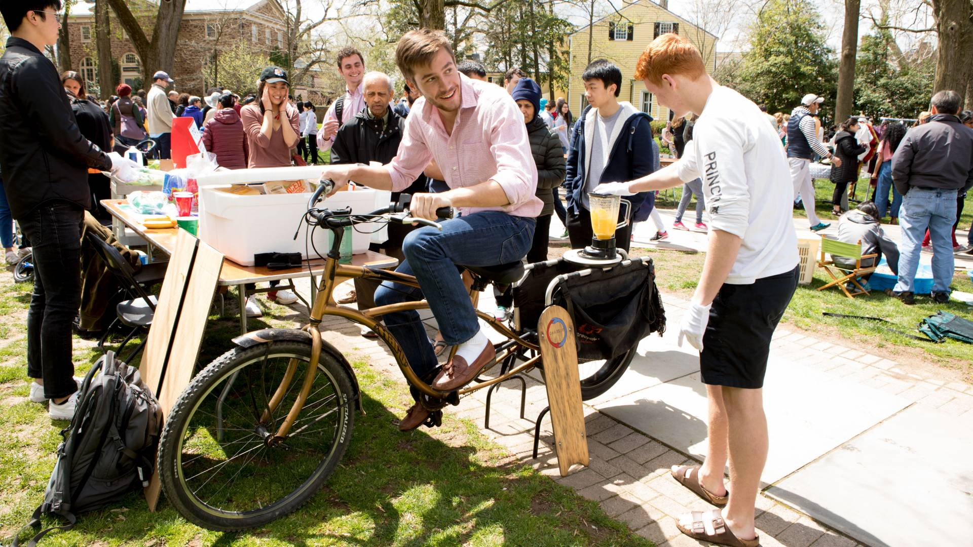Student pedaling bicycle to power up a blender