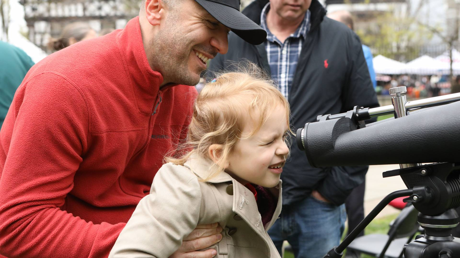 Flip Beranyeh holding Krystina to look through telescope