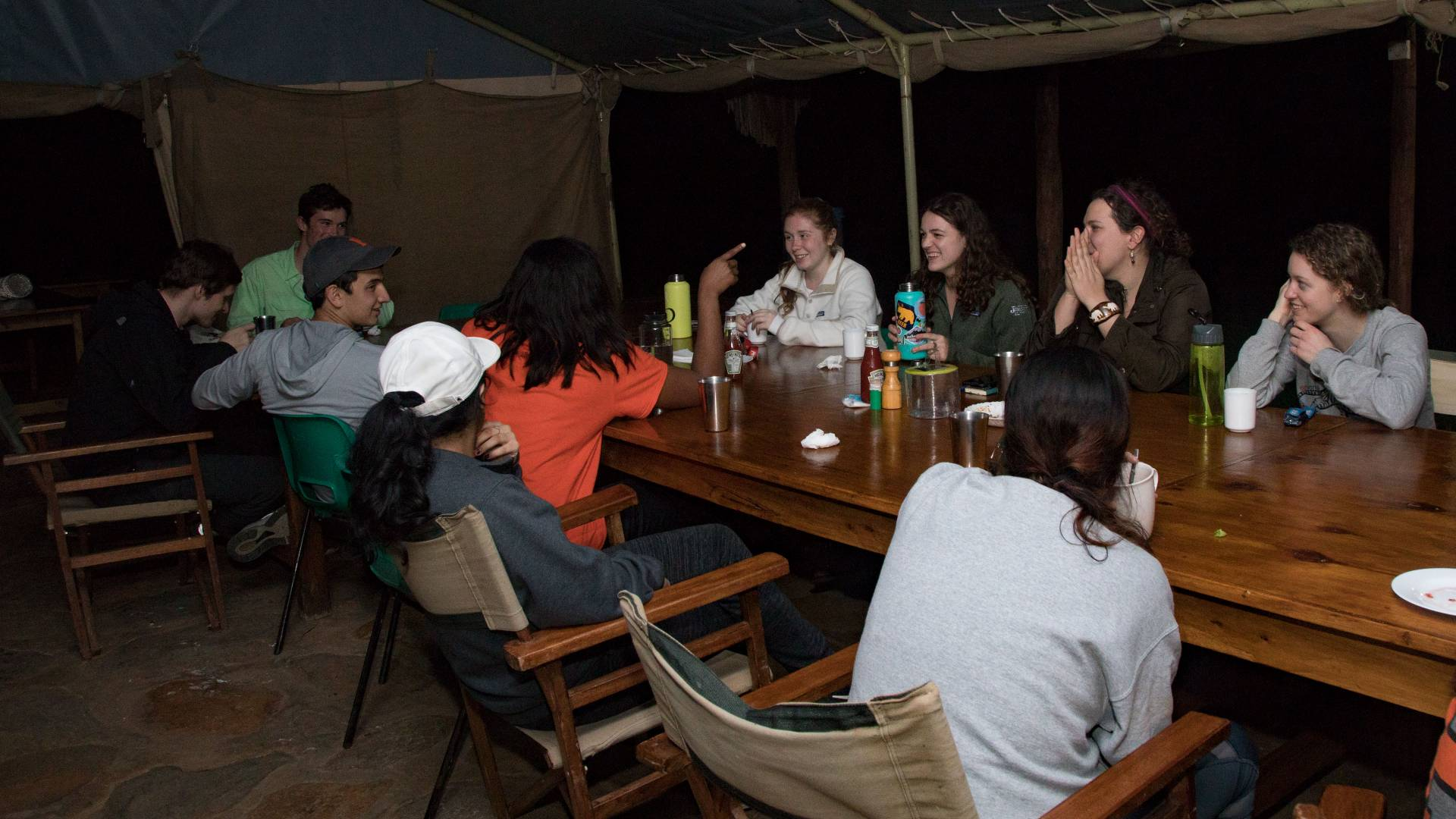Students eating around a table at night at Mpala