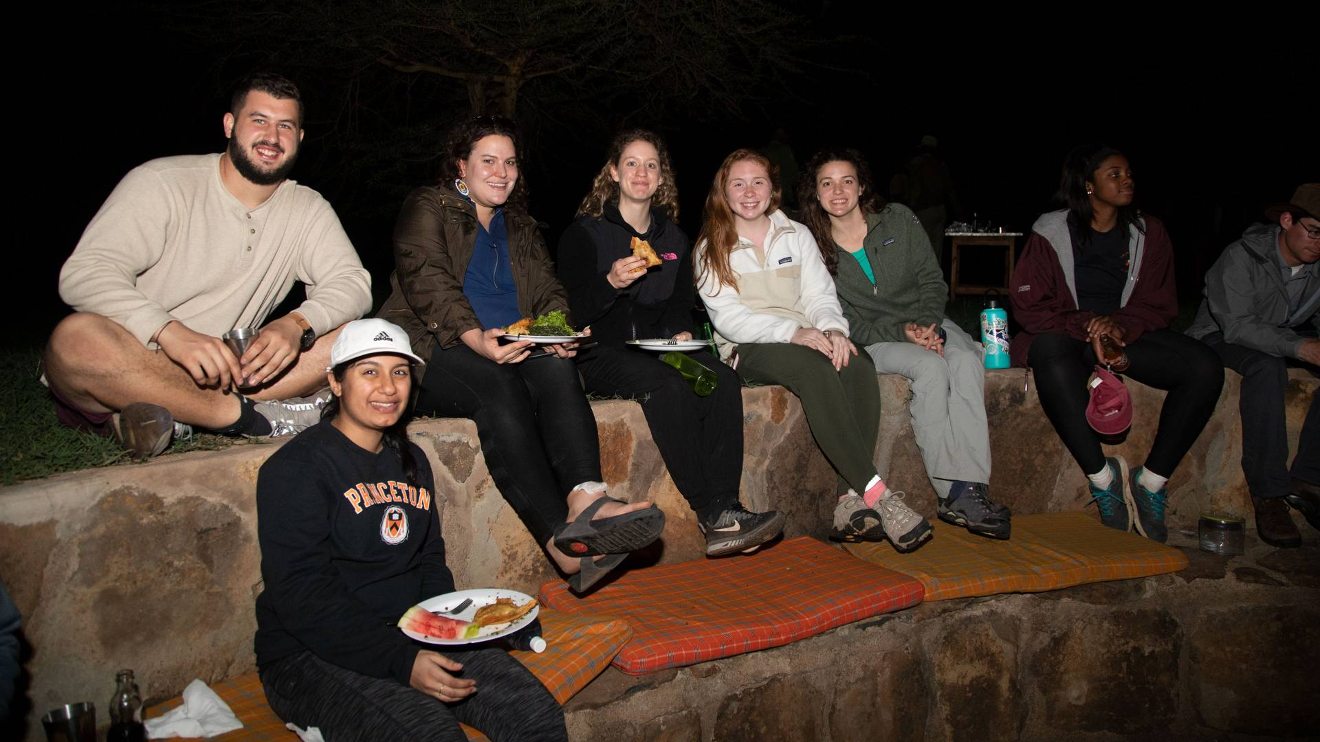 Students sitting around a campfire at night at Mpala