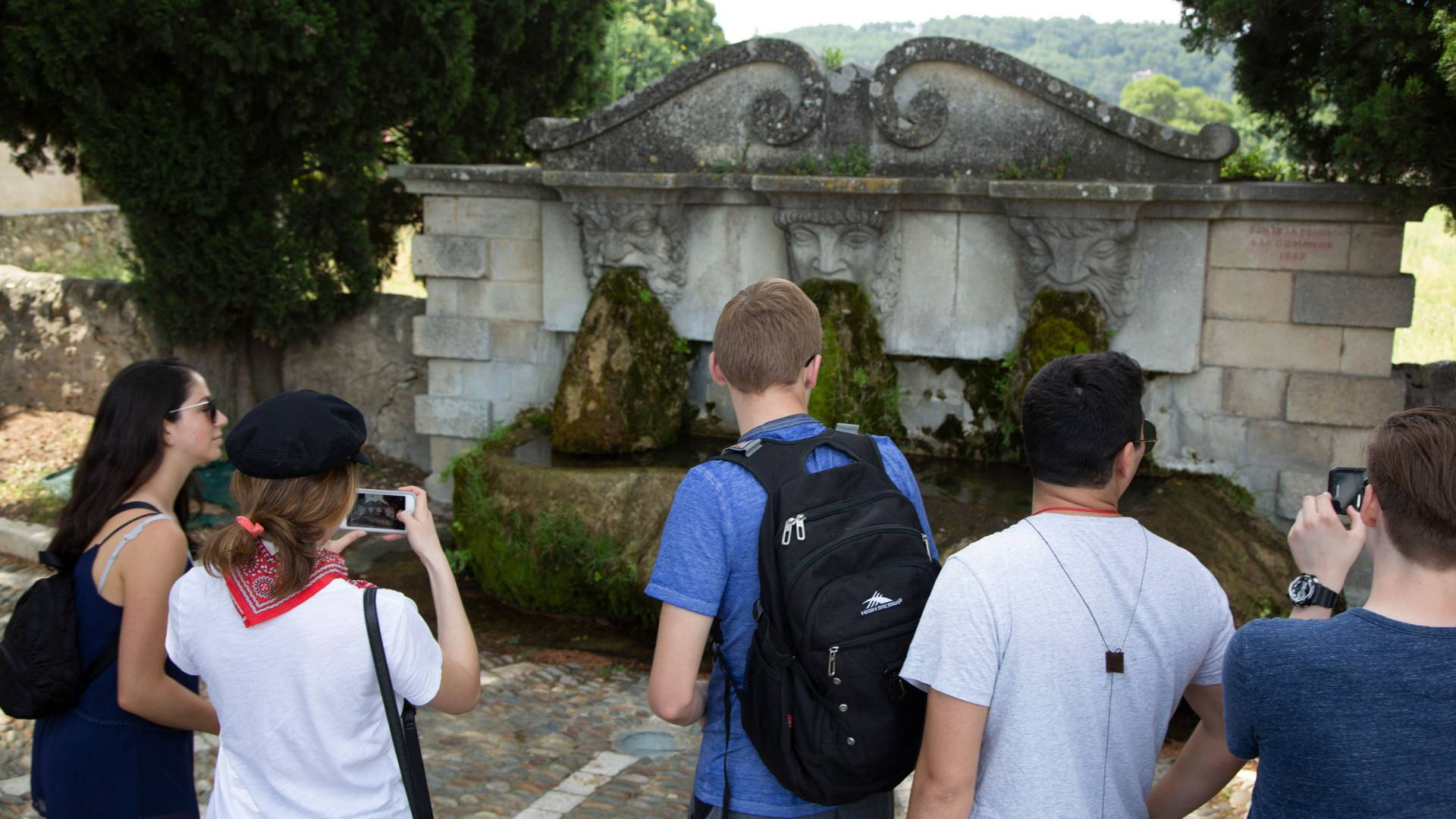 Students looking at fountain with three faced spouts  in France