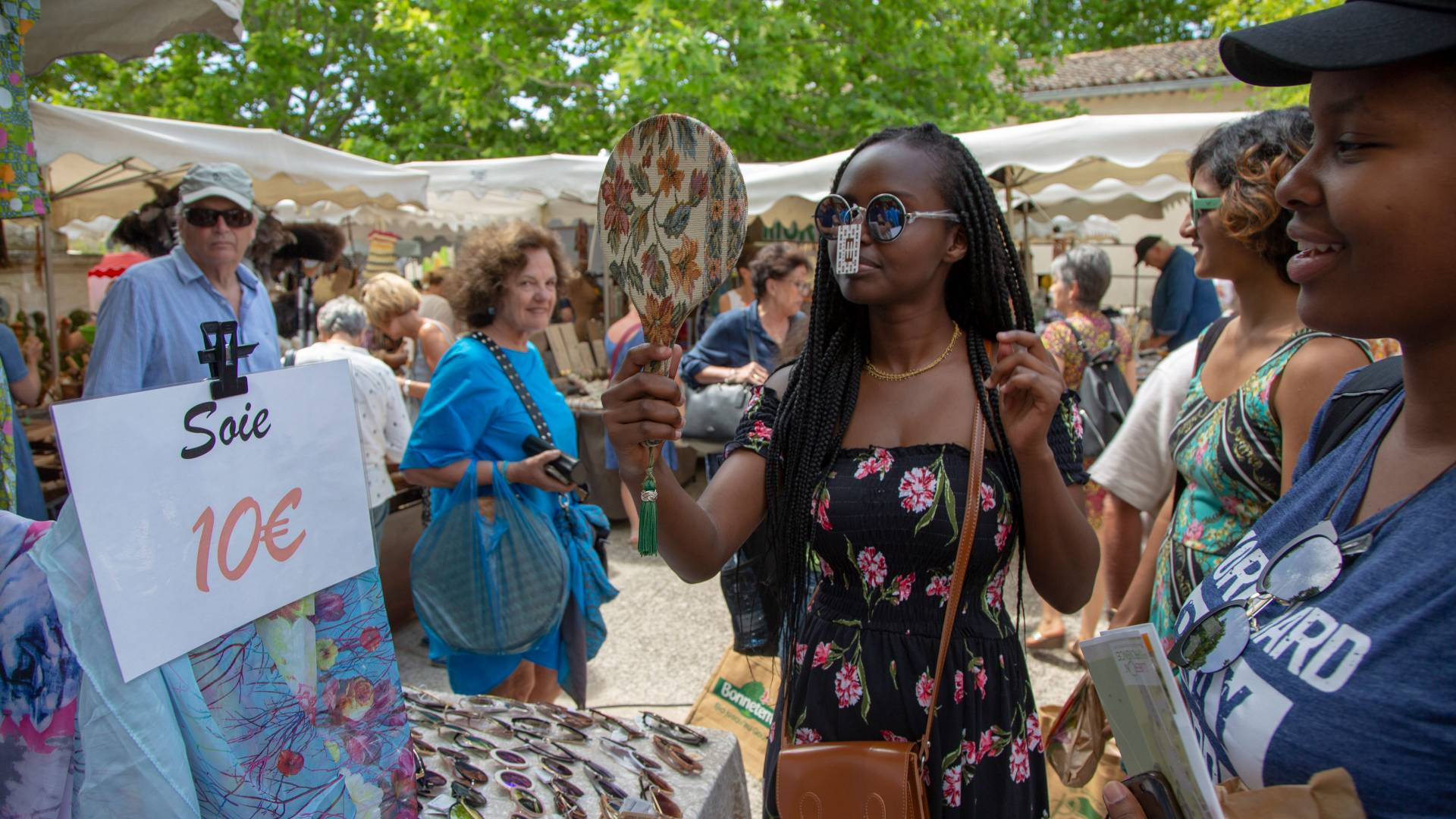 Student trying on sunglasses in outdoor market in France