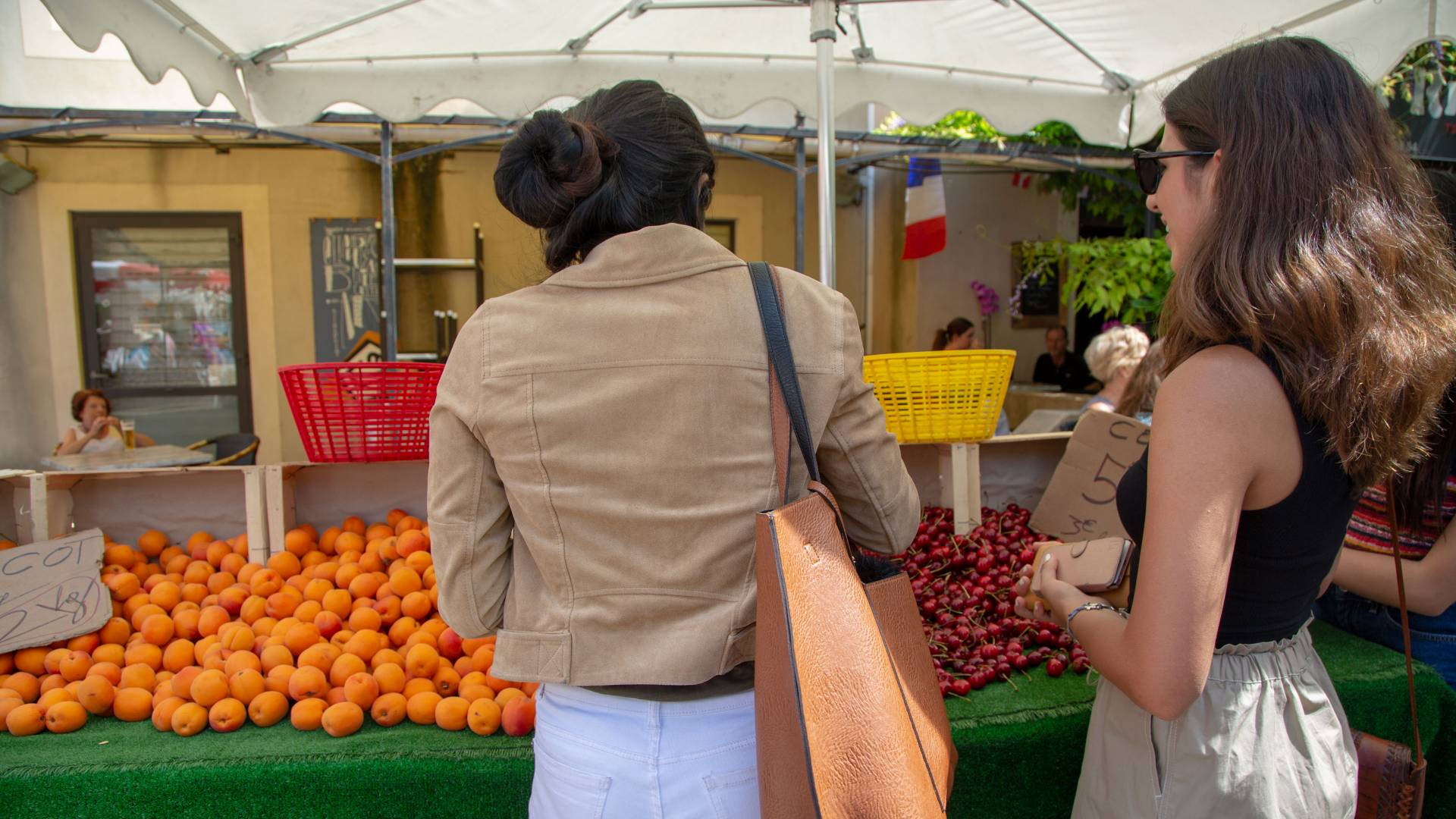 Students looking at fruit in outdoor market in France