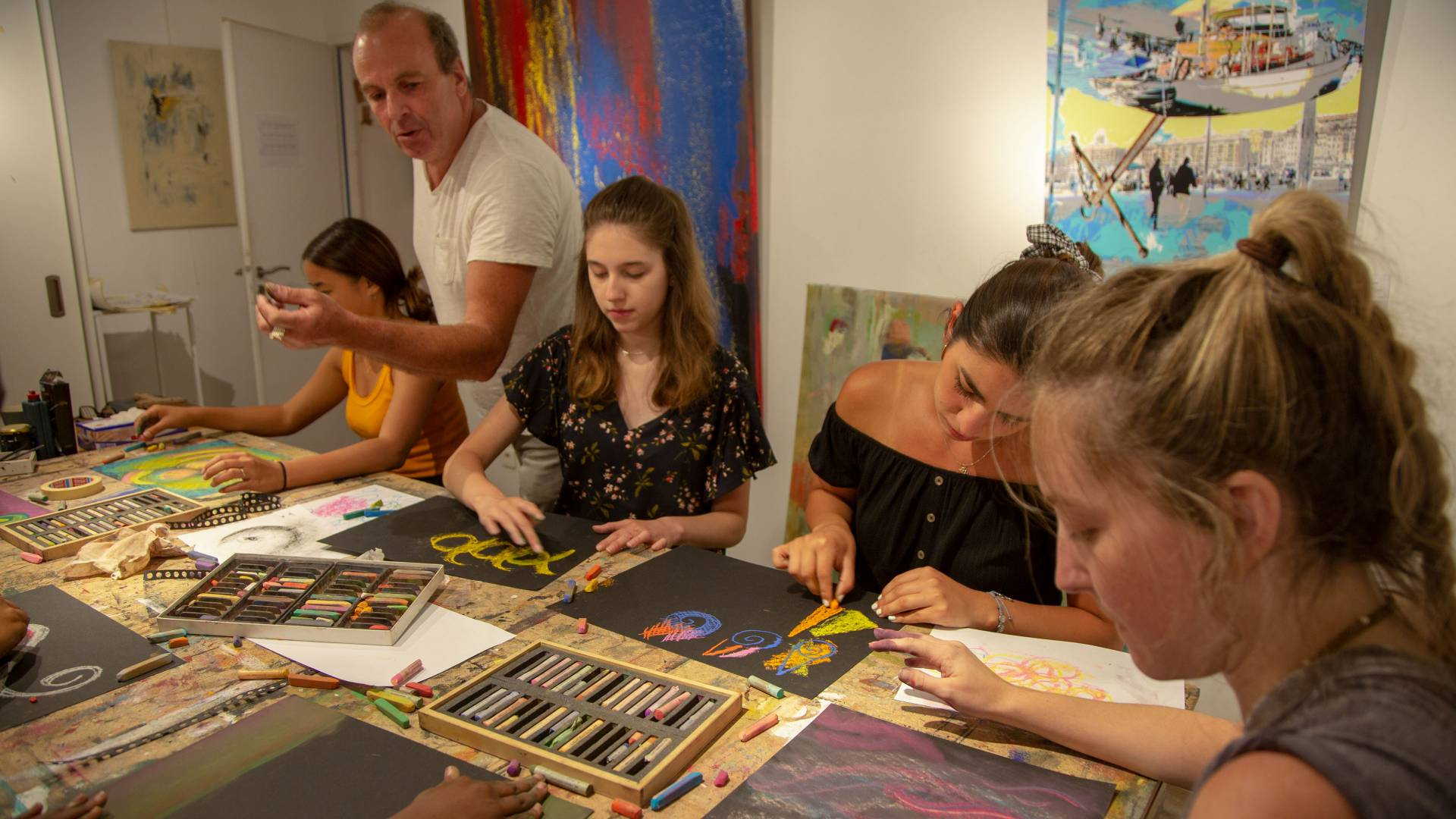 Students working on art projects with instructor in France