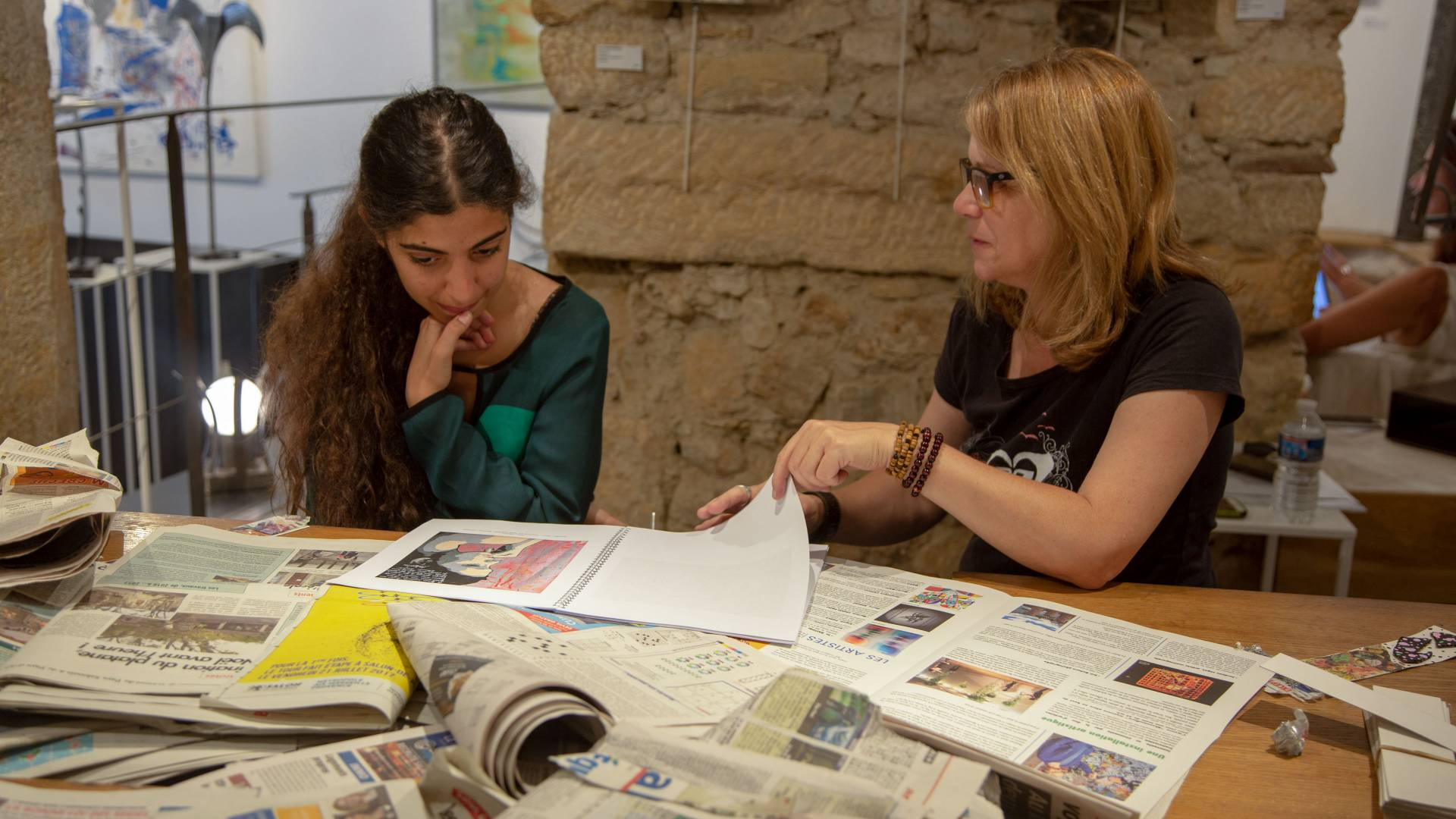 Instructor and student looking at newspapers in France