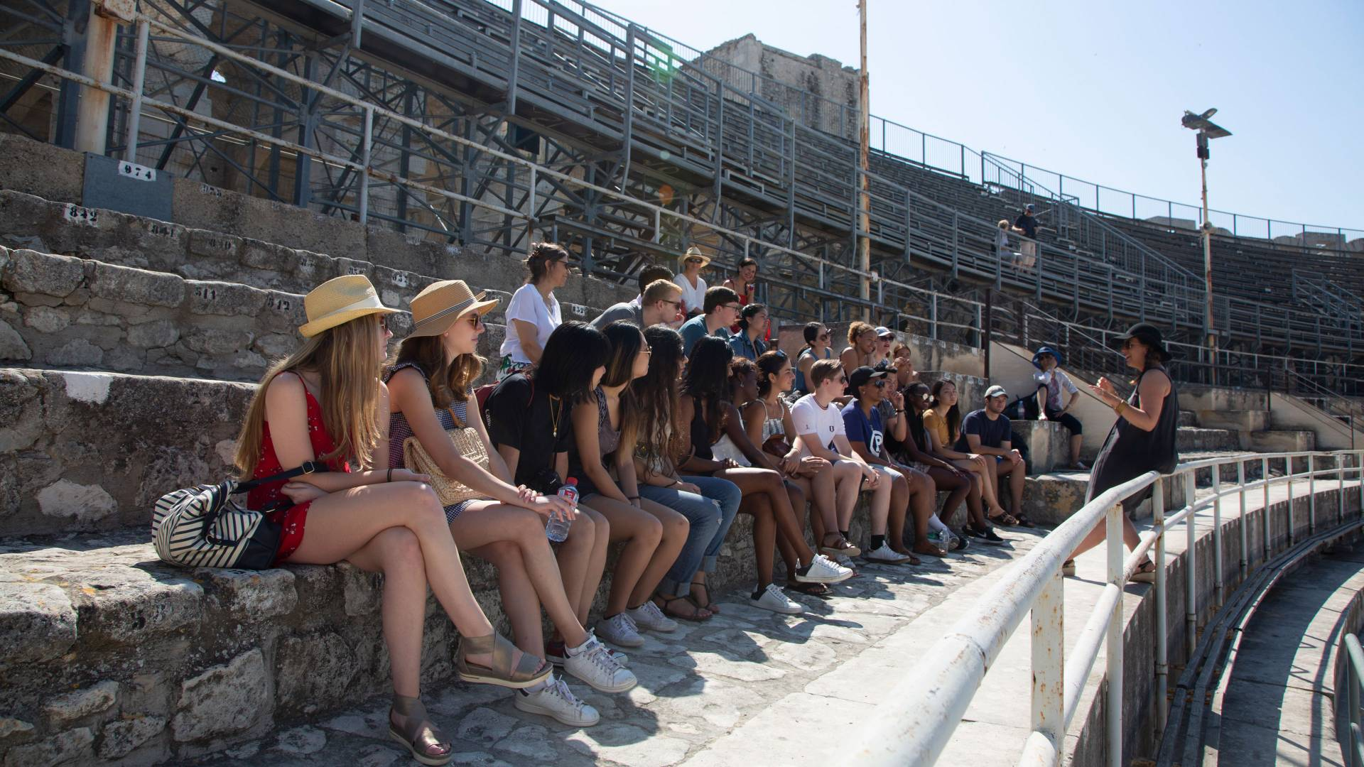 Students sitting on bench at amphitheater in Arles, France