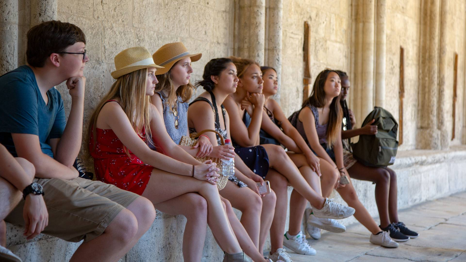 Students sitting against wall in Arles, France