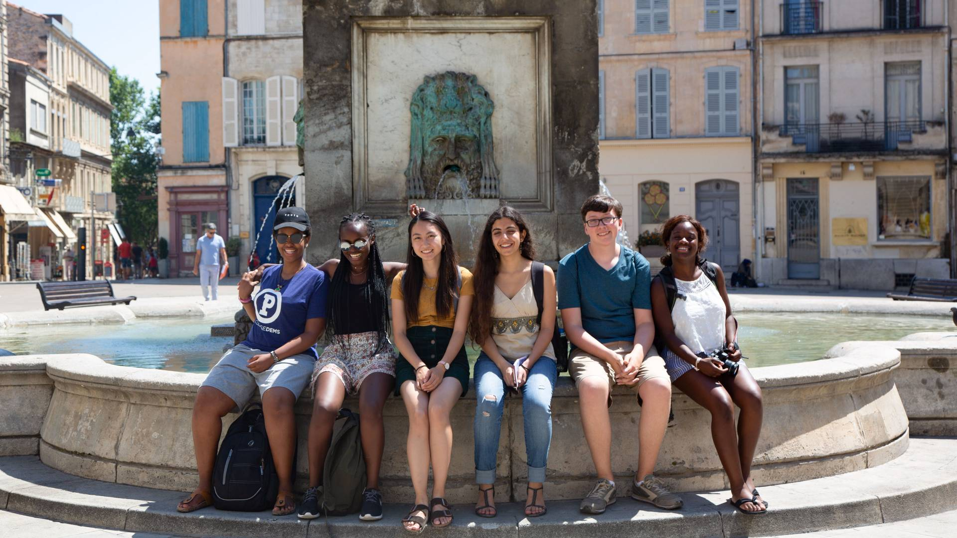 Students sitting at fountain in Arles, France