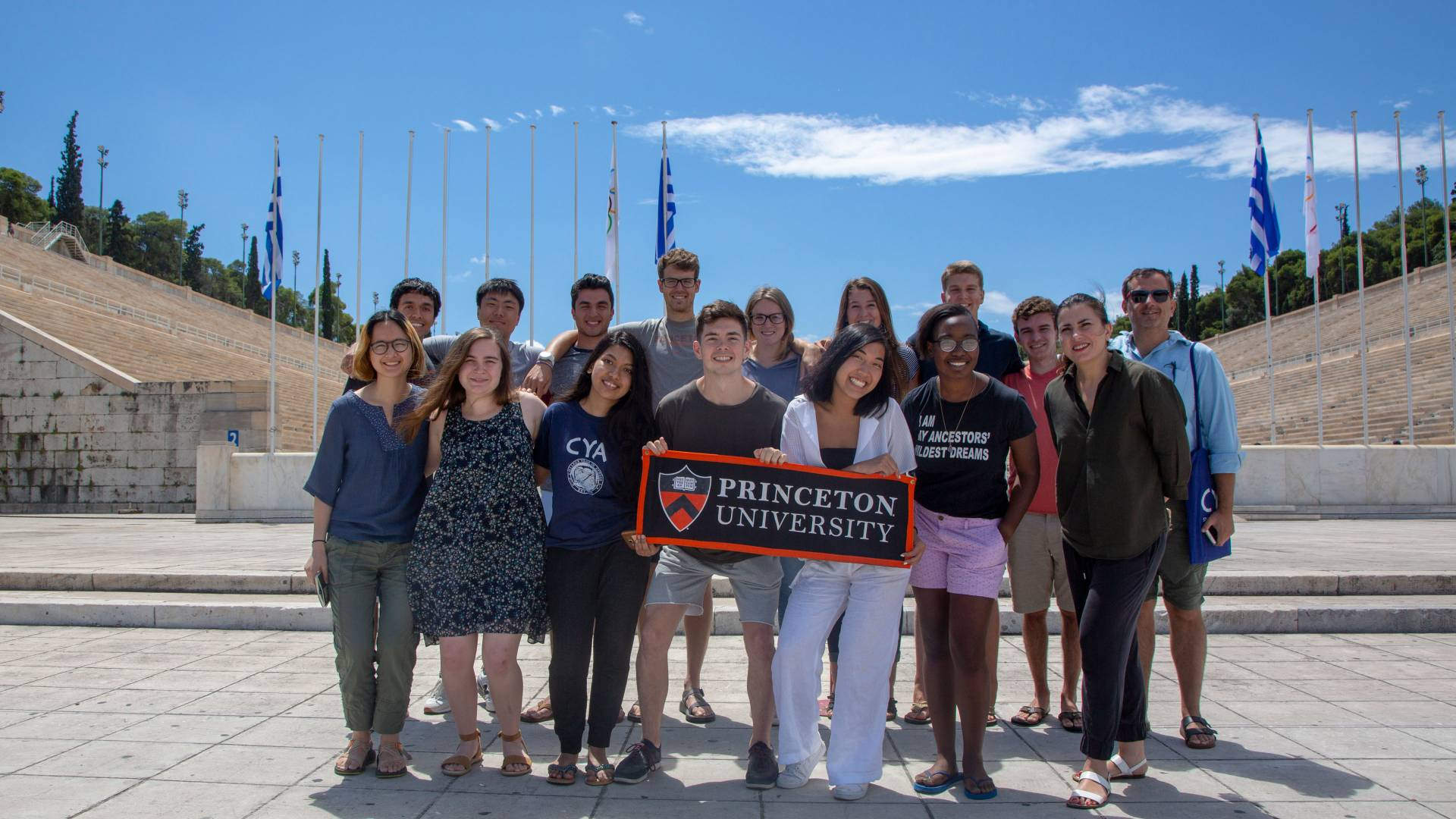 Students and professor standing in front of stadium holding Princeton University banner