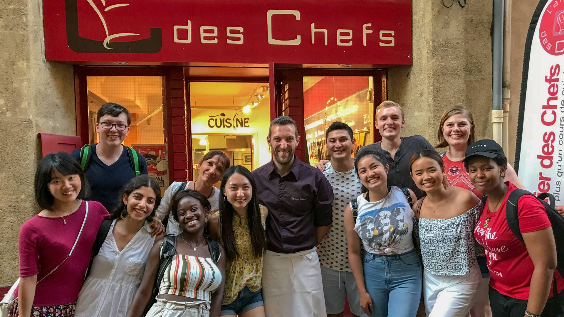 Students and chef posing outside cafe in France
