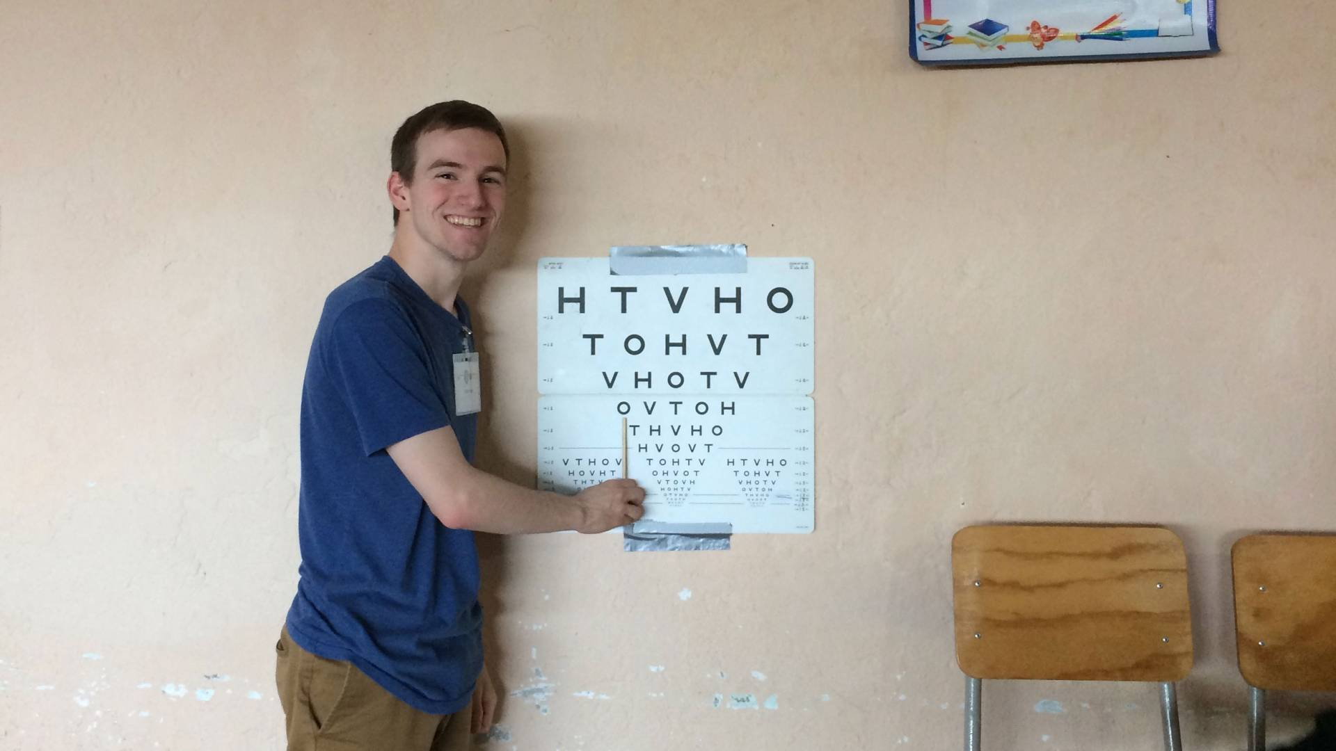 Student pointing to eye chart taped to wall