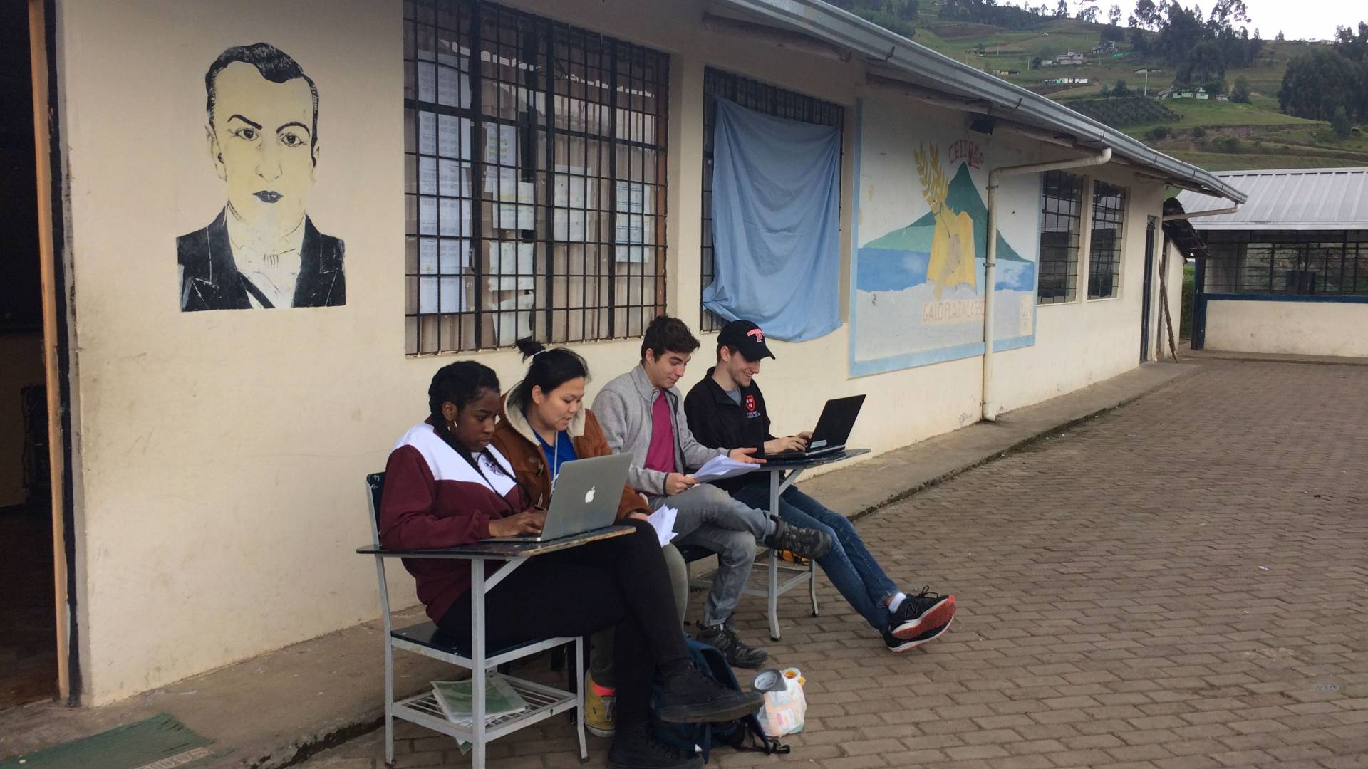 Students working on laptops outside in Ecuador