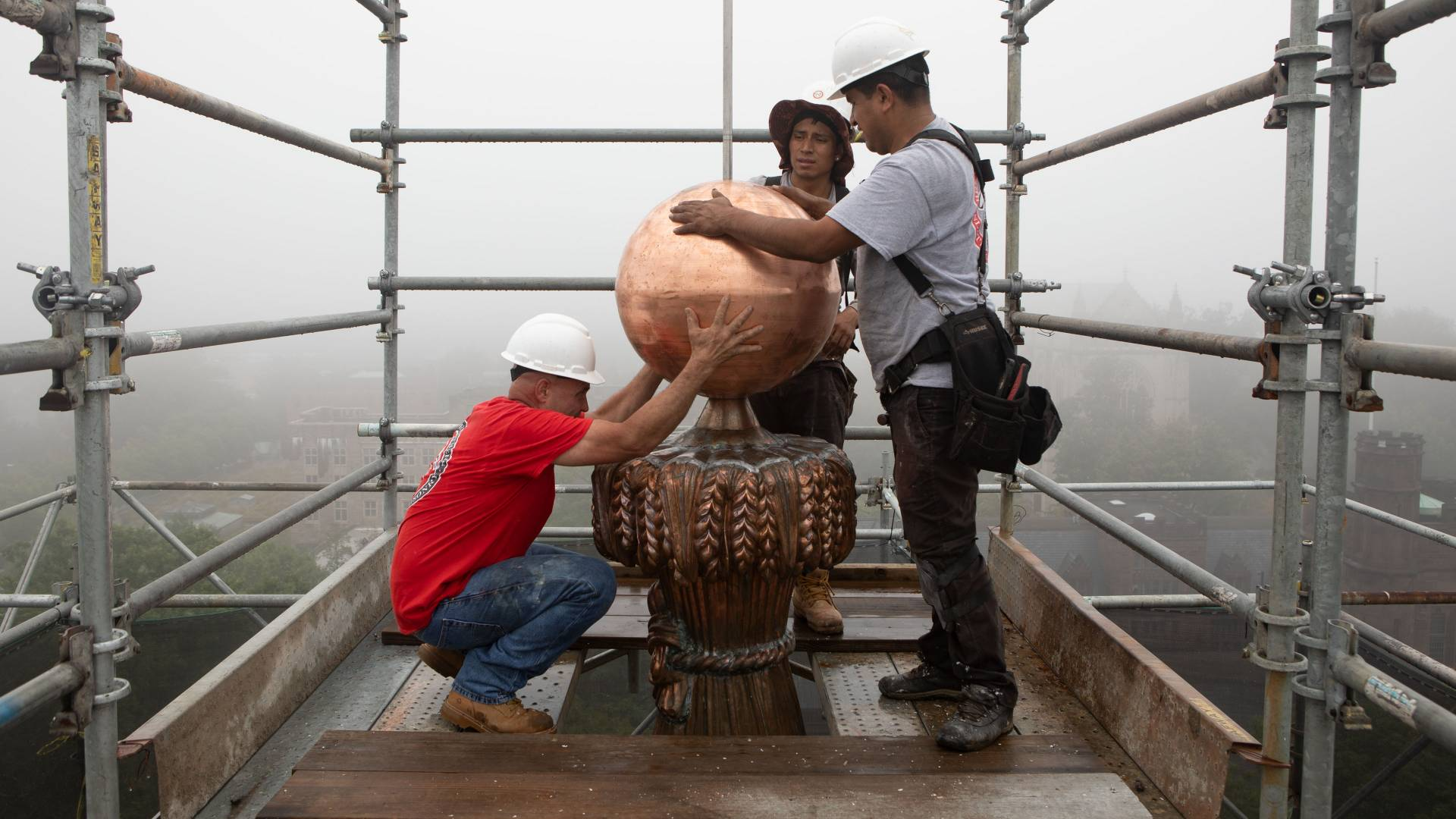 Workers assembling copper wheat-sheaf column and ball on top of Nassau Hall cupola