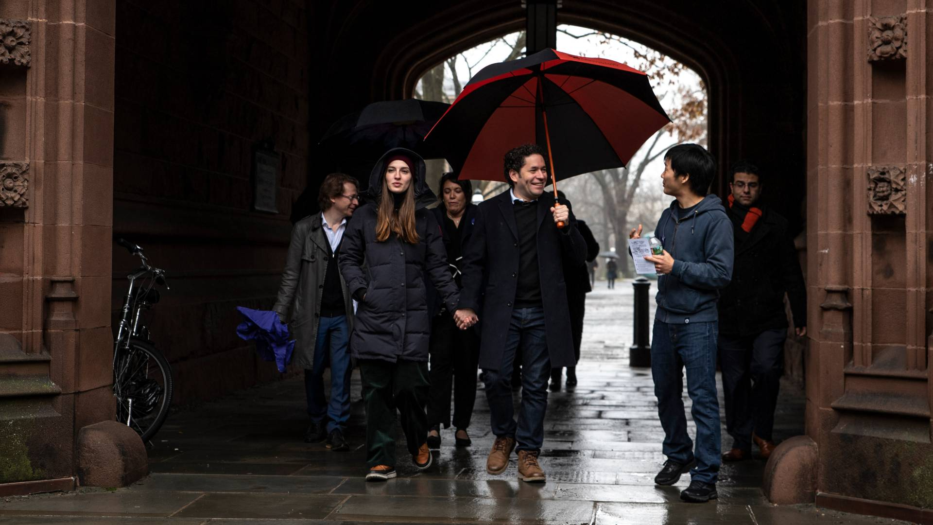 Gustavo Dudamel and people walking through Princeton archway