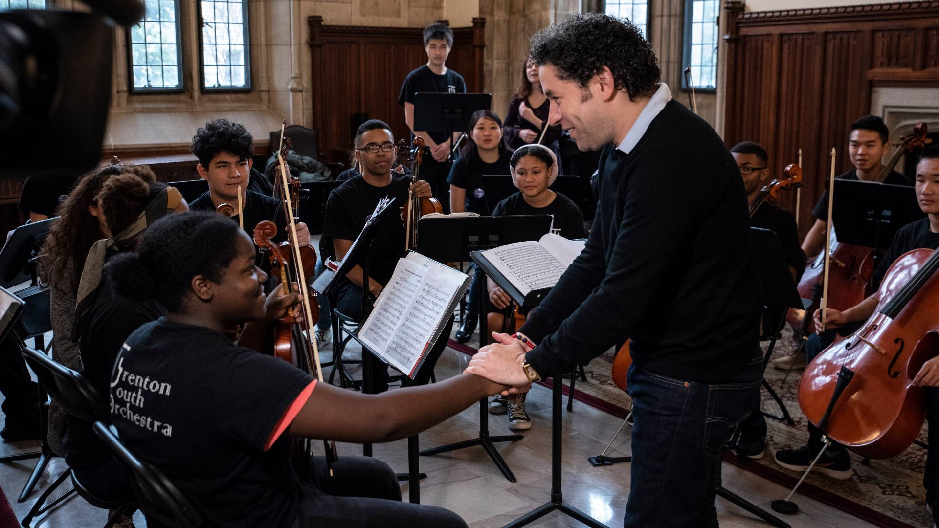 Gustavo Dudamel shaking hands with violinist
