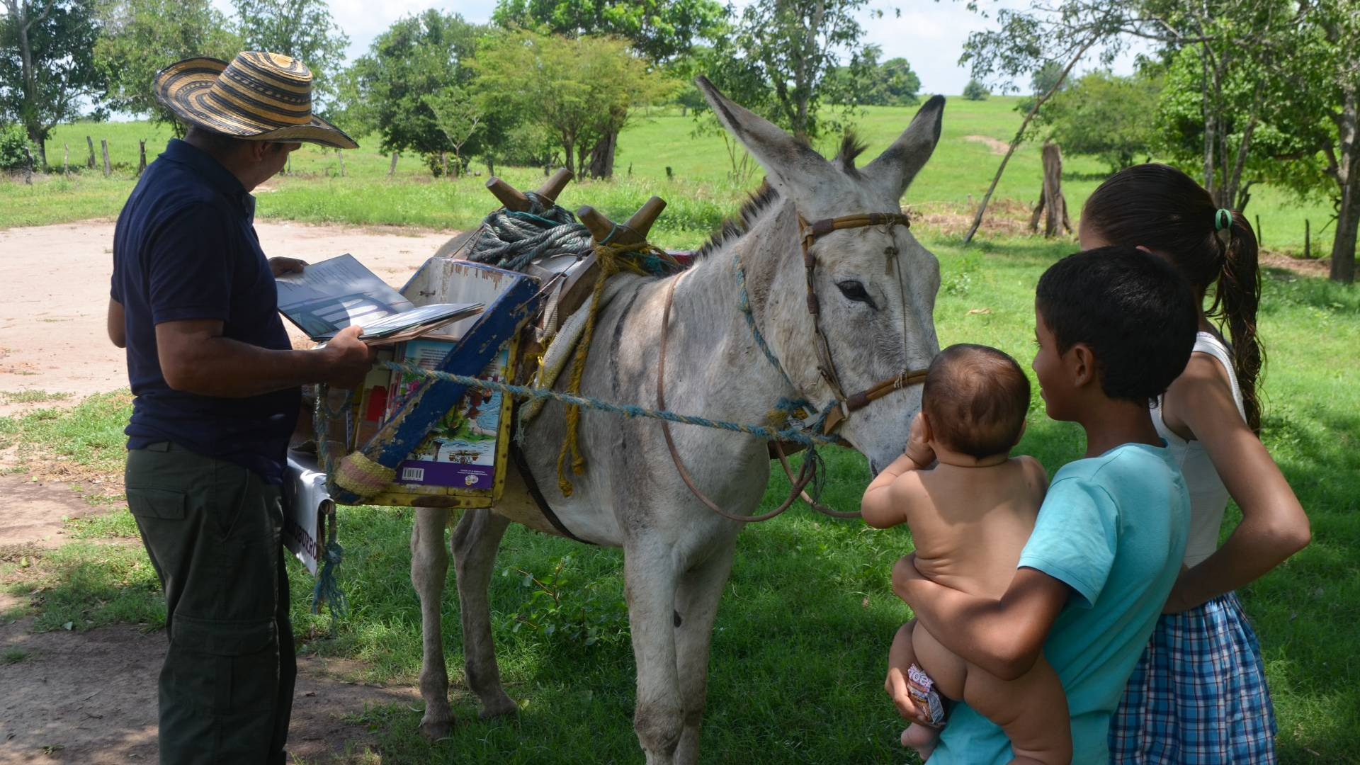 Man reading book in front of burro and three children