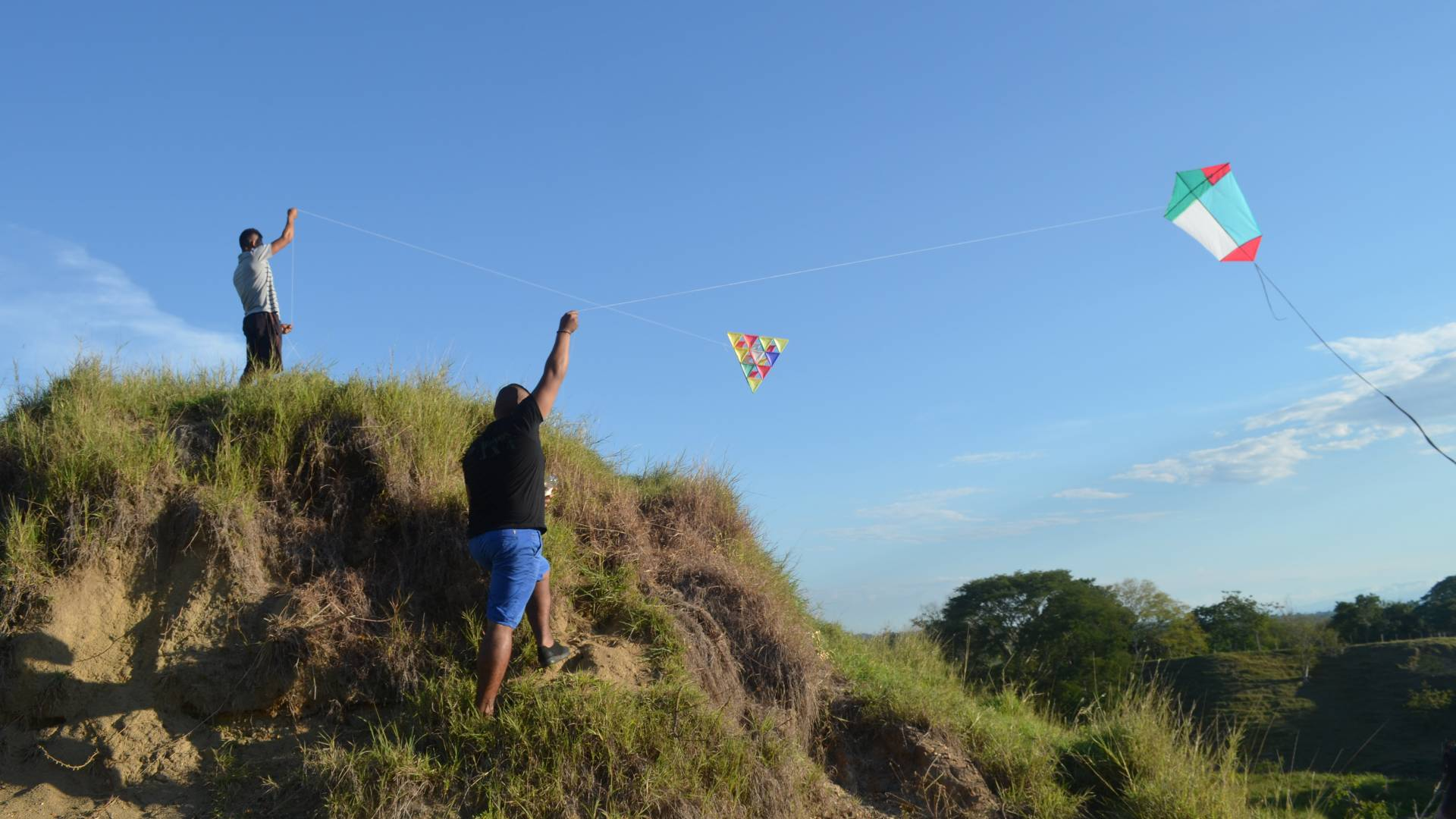 Two men flying kites on hill top