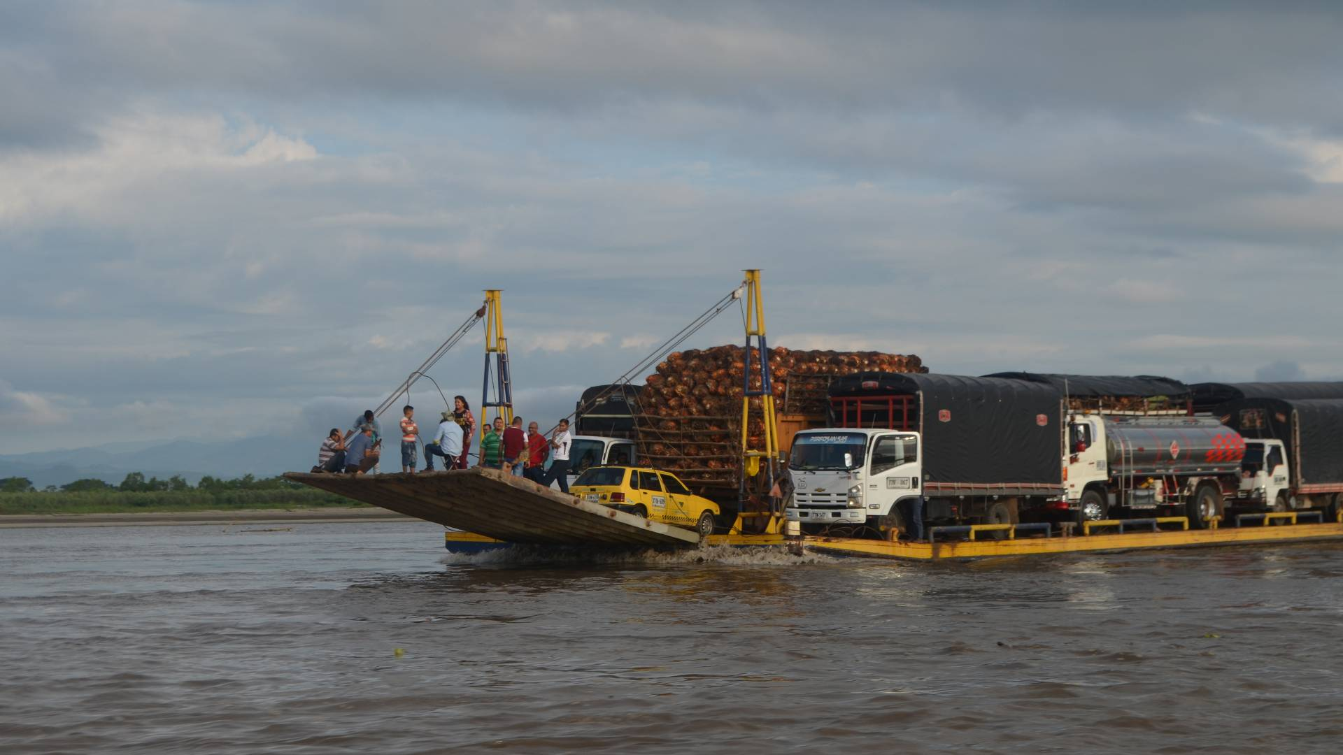 Barge filled with cars, trucks and people going across river