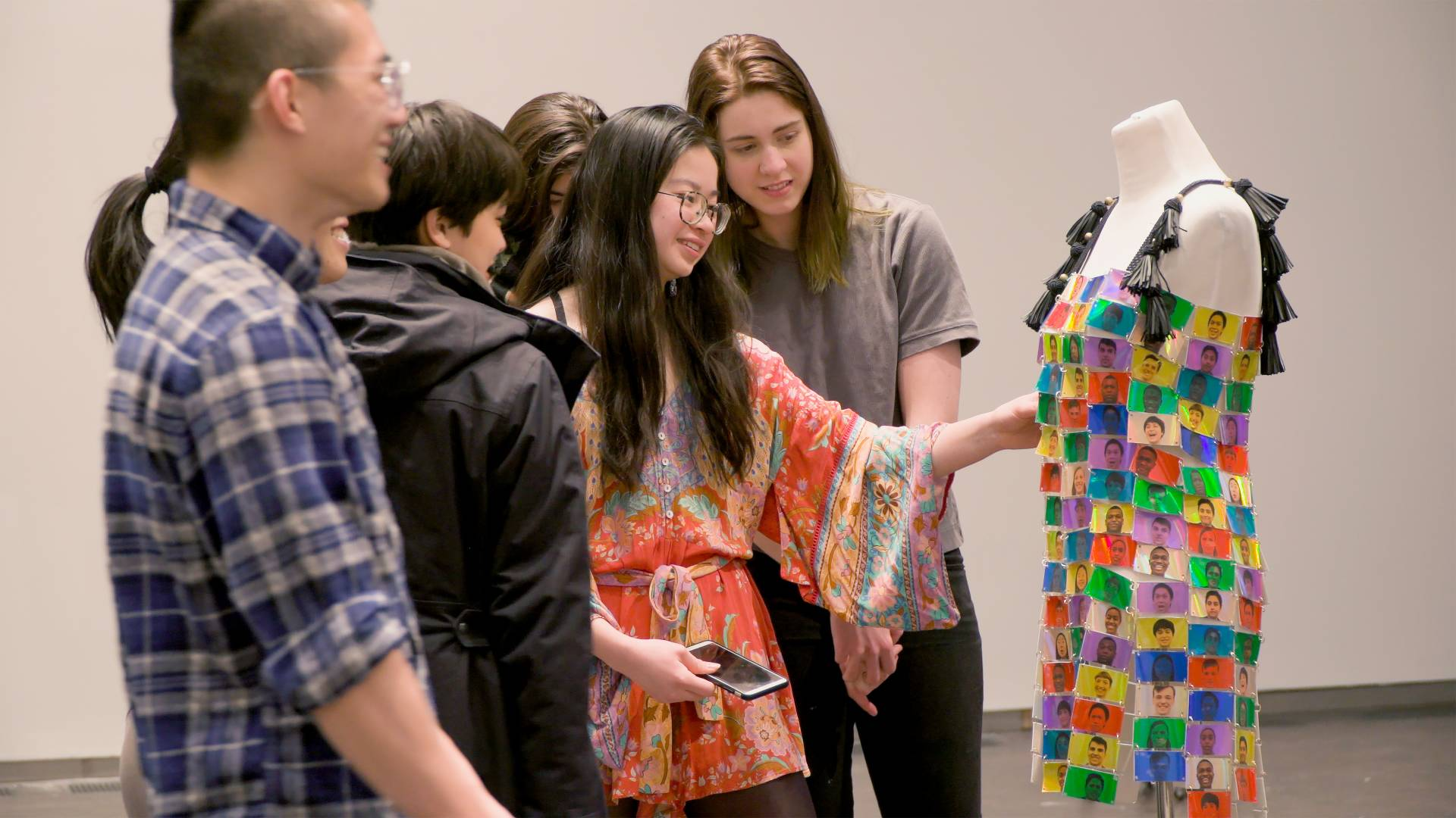 "Jessica Zhou (center) discusses her multi-colored ""emotions"" dress with a group of other students"
