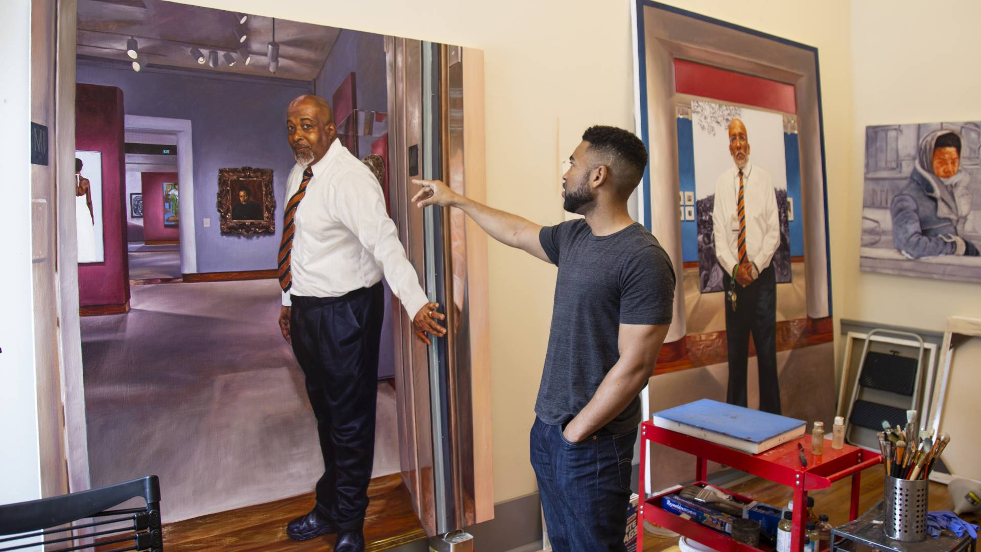 Mario Moore in studio pointing at painting