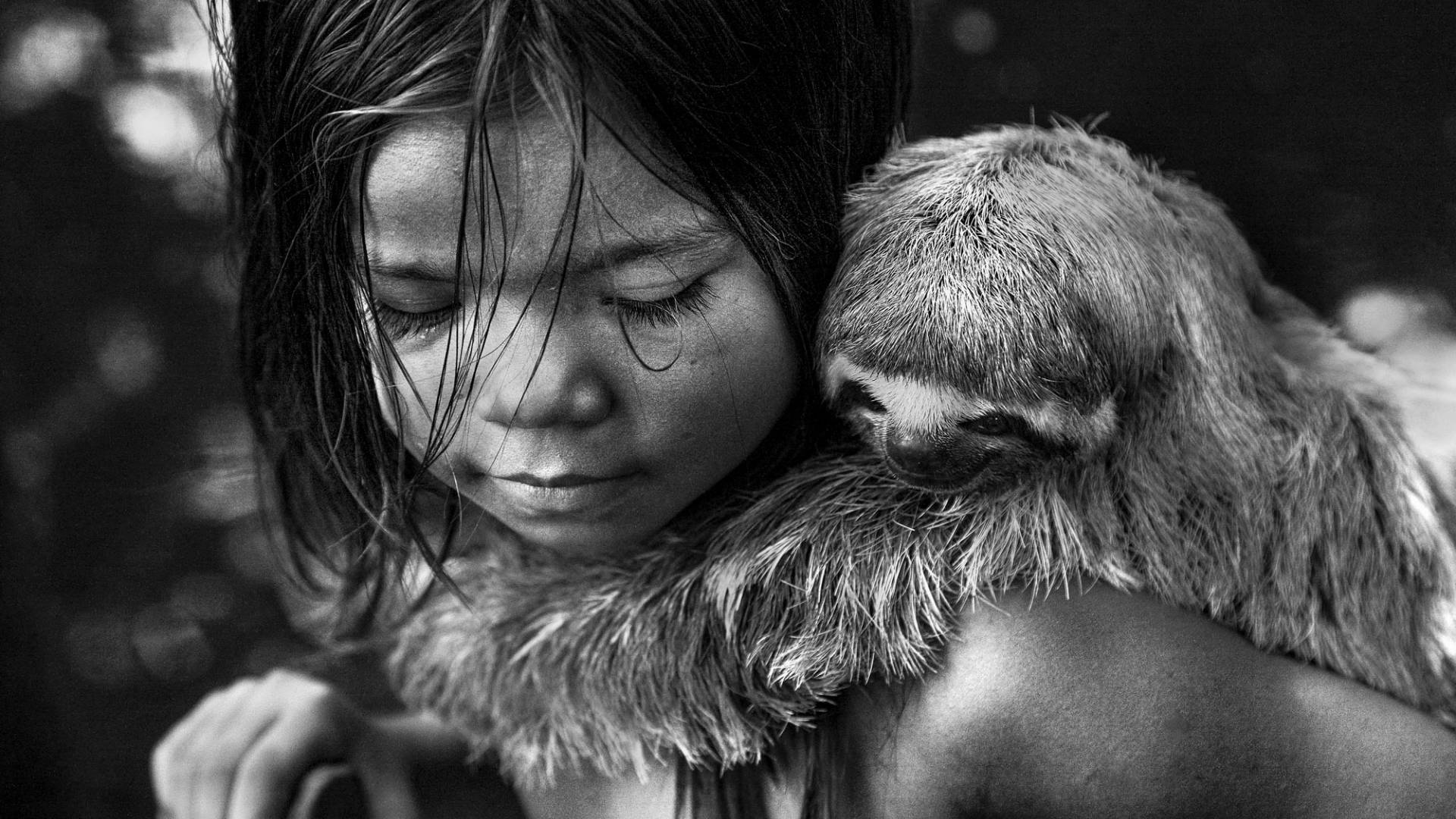 A young girl with a sloth holding onto her back