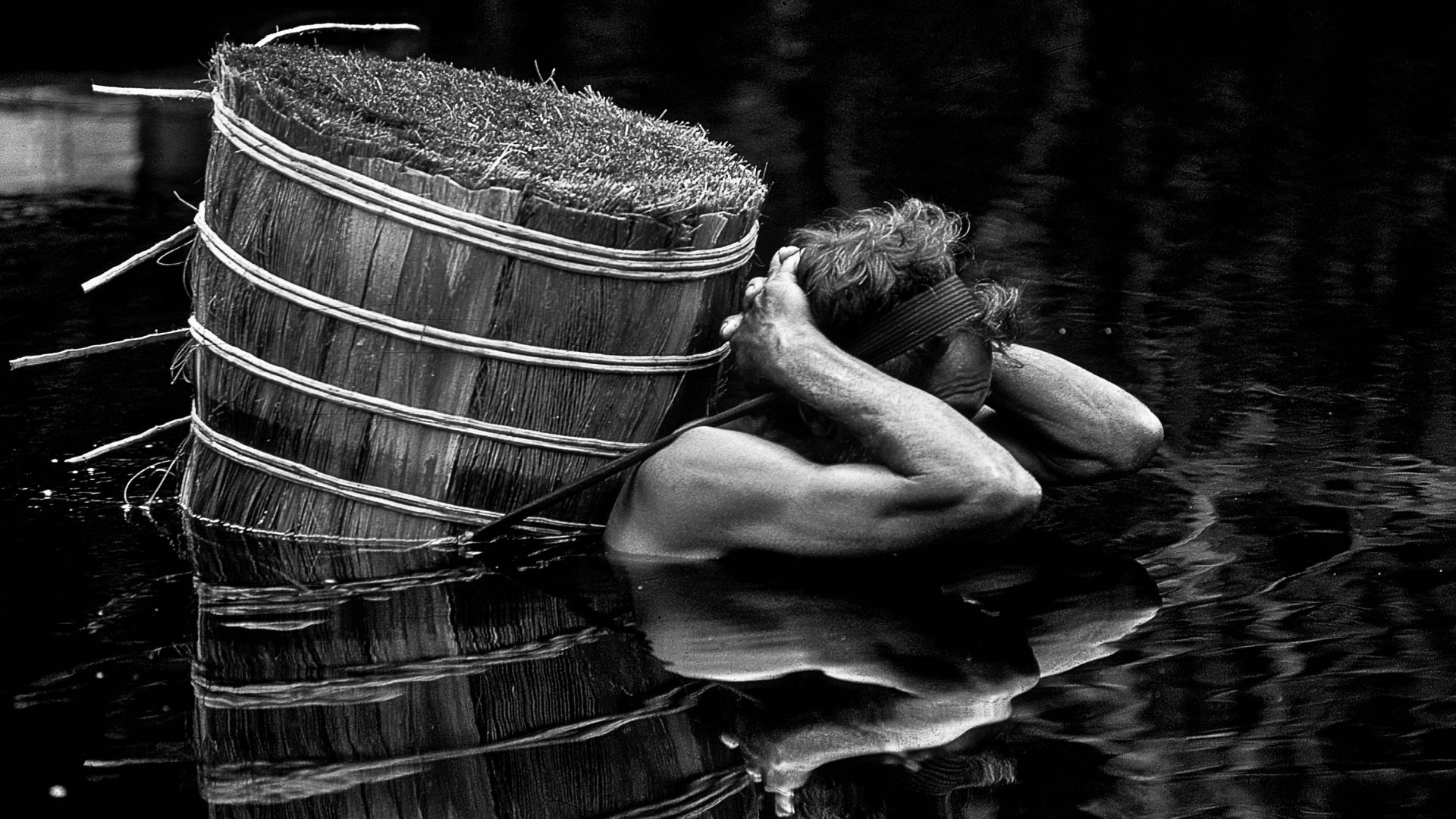 A man in water carying a barrel on his back