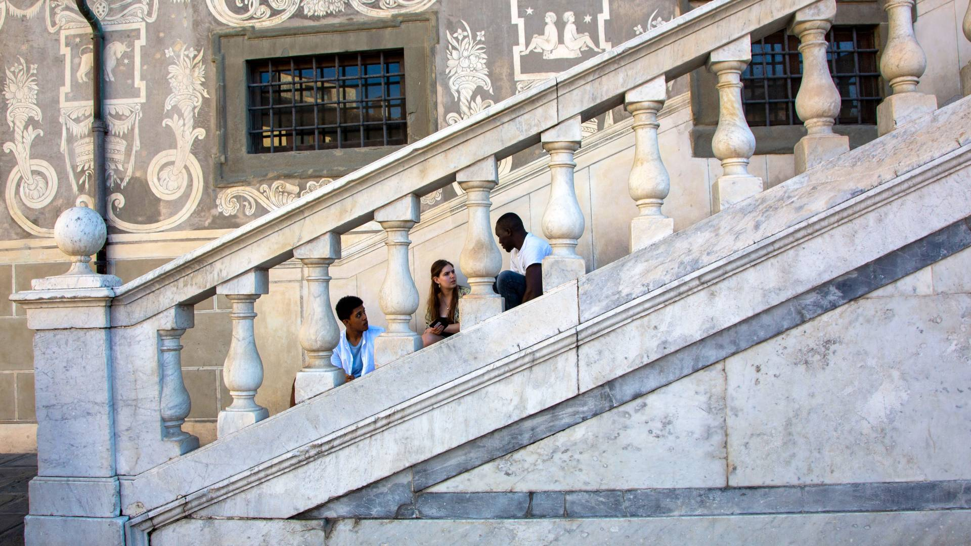 Three students sitting on steps