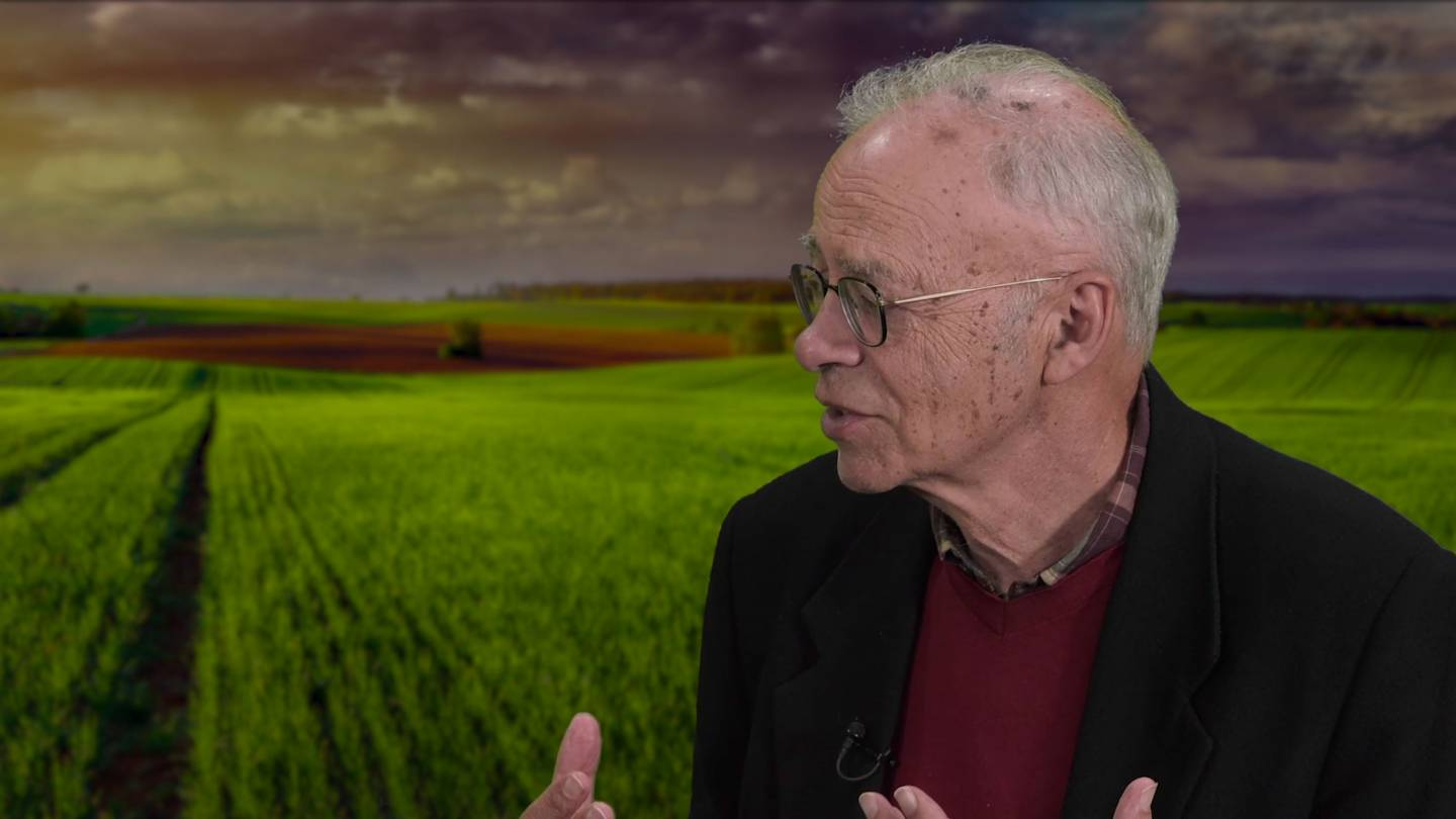 Peter Singer Speaks in front of a farm backdrop