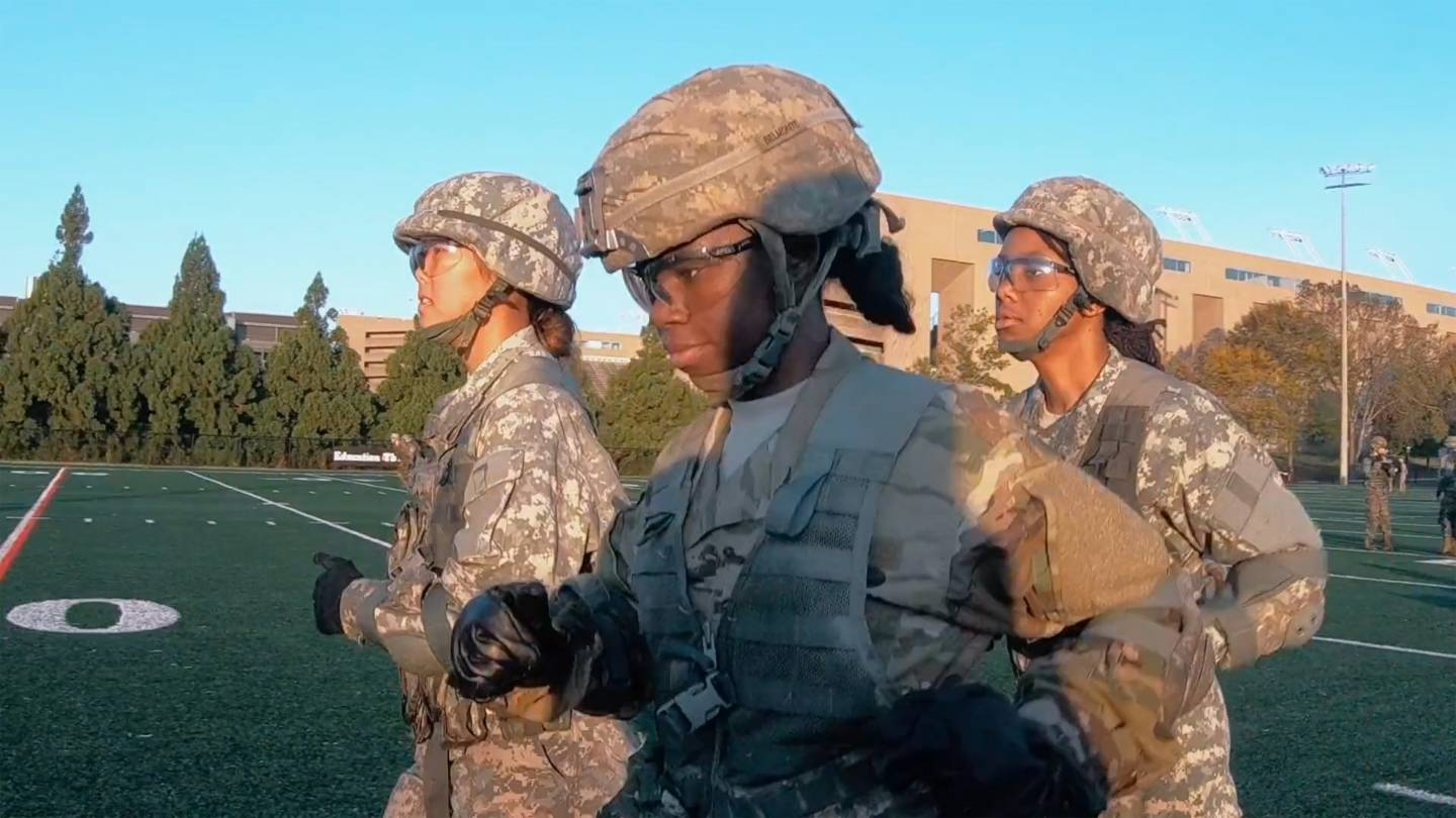 3 students run in a field in military fatigues