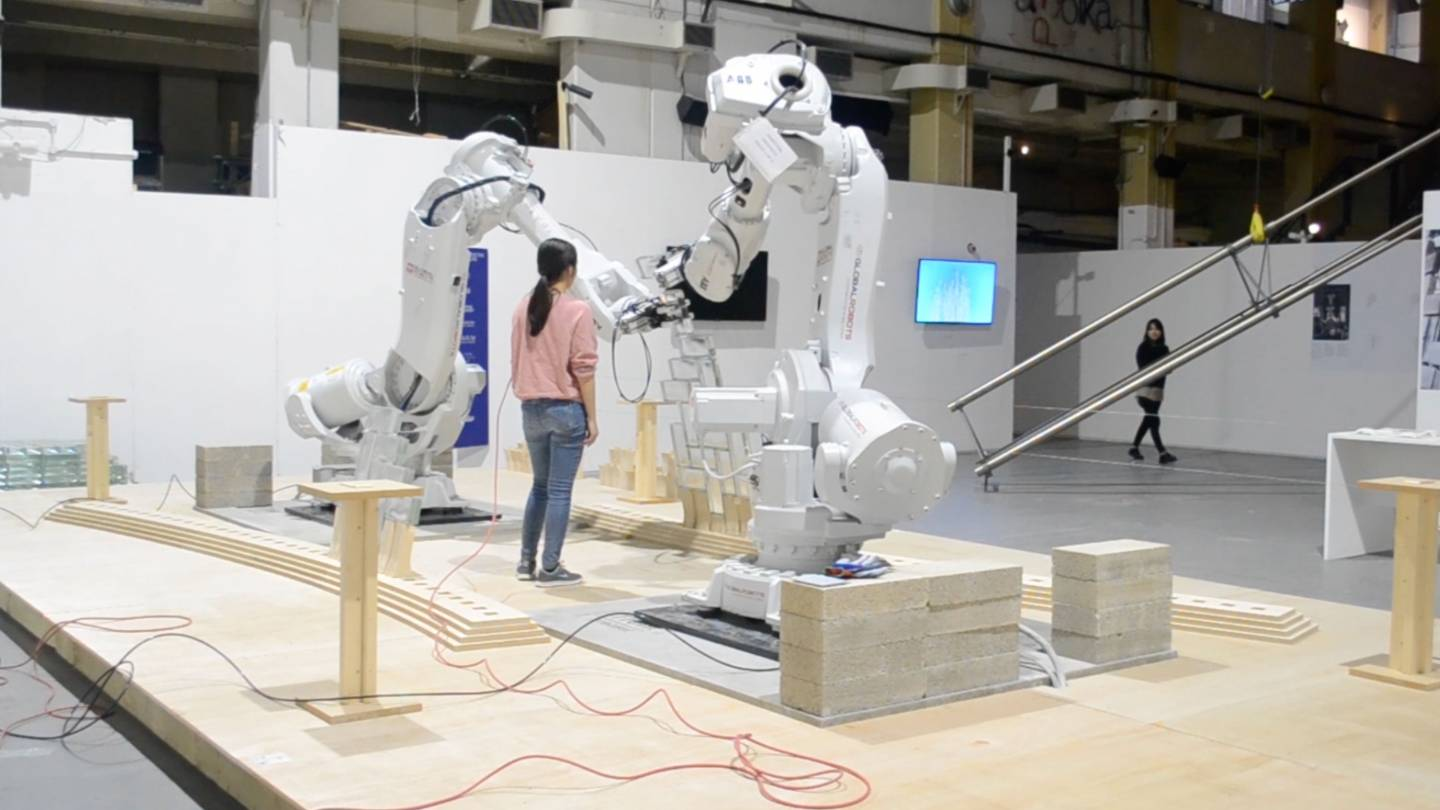 a students watches the two robots work