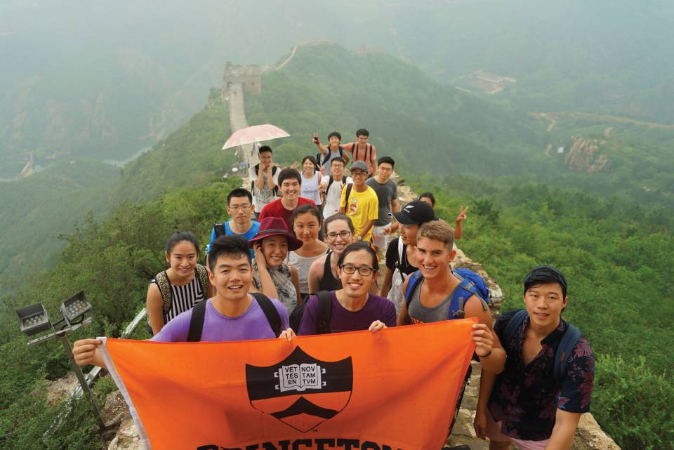 Students stand together and hold a Princeton University flag on the Great Wall of China