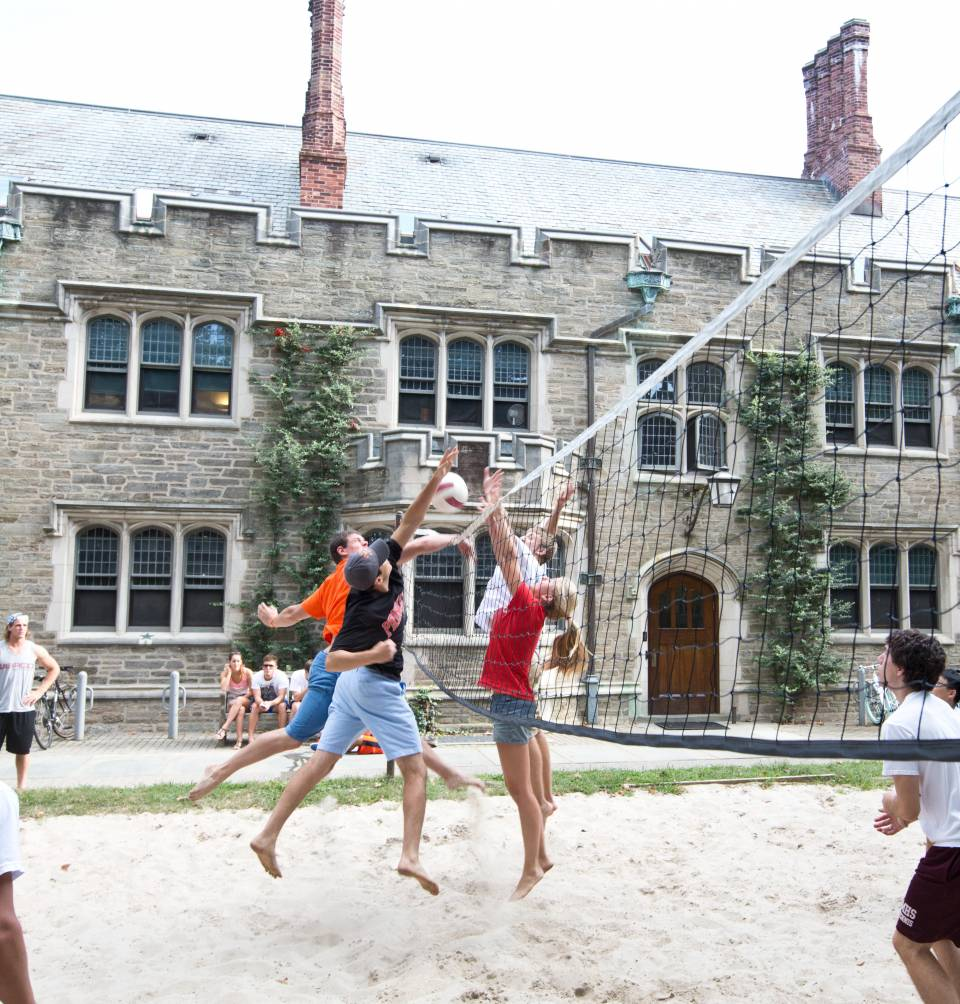 Students playing volleyball on sand court