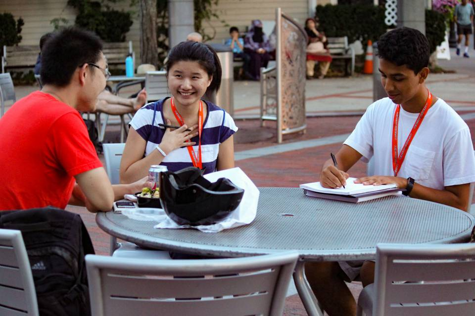 Students interviewing person sitting at outside cafe