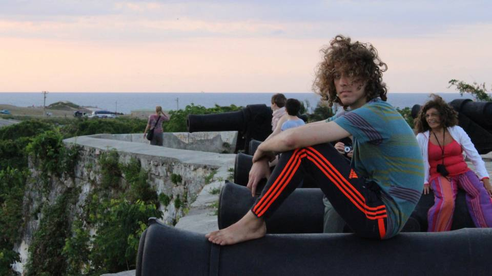 Kyle Berlin sitting on cannon in Cuba