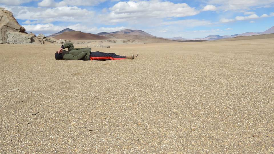 Kyle Berlin lying in dirt field in Uyuni, Bolivia