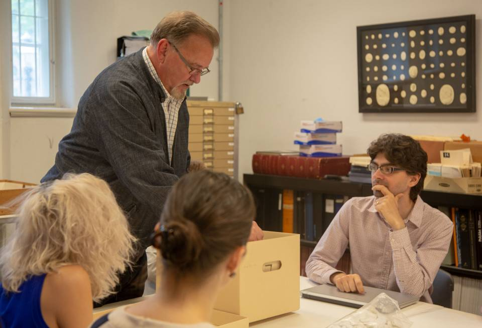 Michael Pagett with graduate students looking at documents from Art Museum