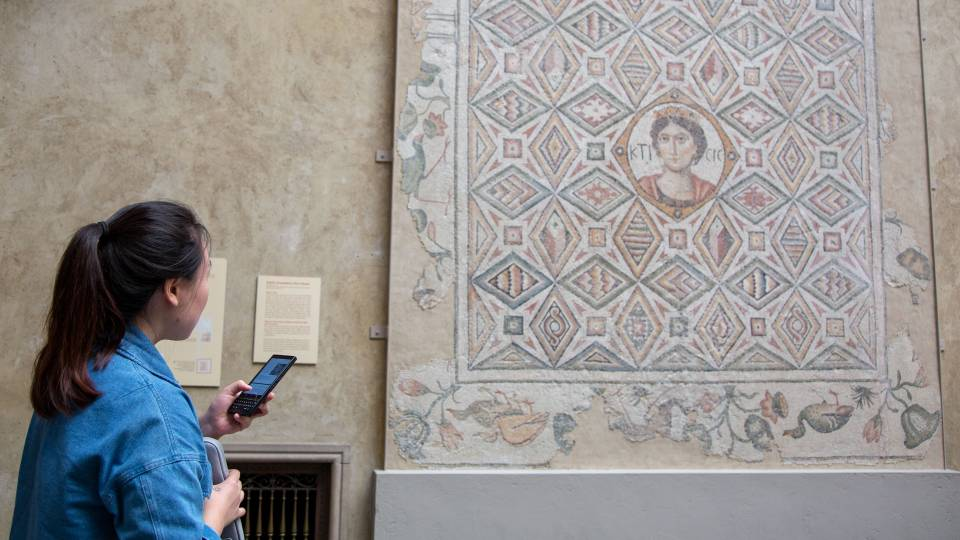 Student looking at large mosaic on wall at Worcester Art Museum