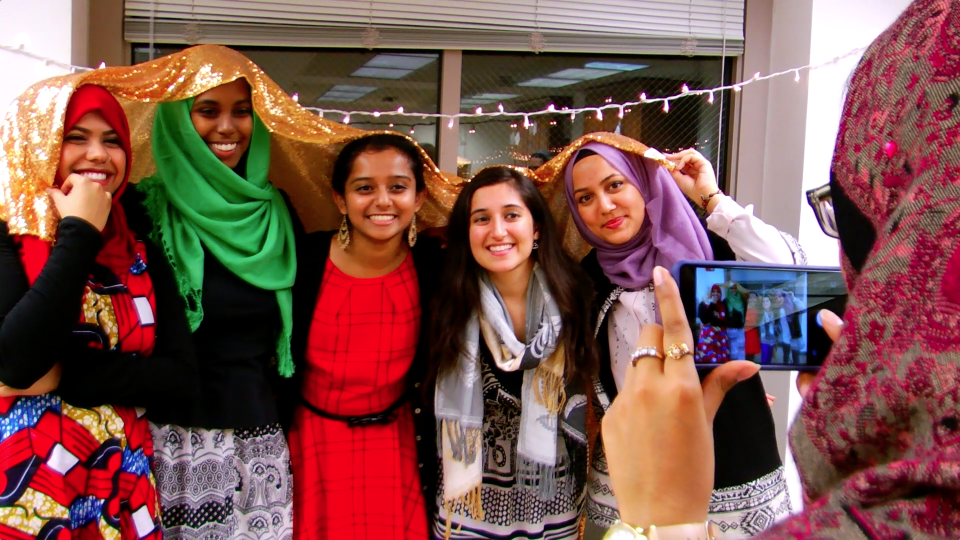 Students posing for photographer at Muslim Life event