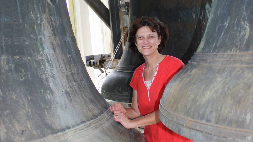 Lisa Lonie amid the carillon bells atop Cleveland Tower at the Graduate College.
