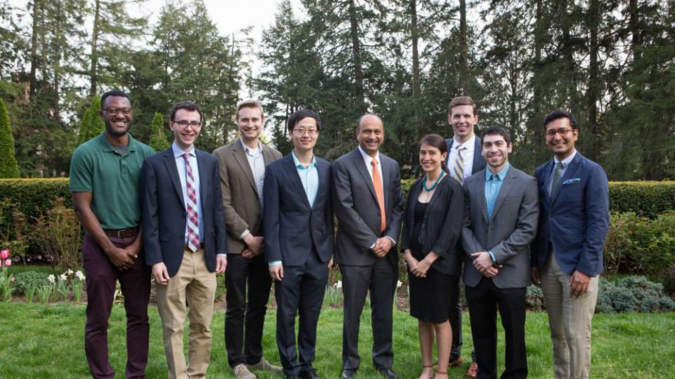 Graduate school teaching honorees pose with Dean of the Graduate School Sanjeev Kulkarni, standing on a lawn.